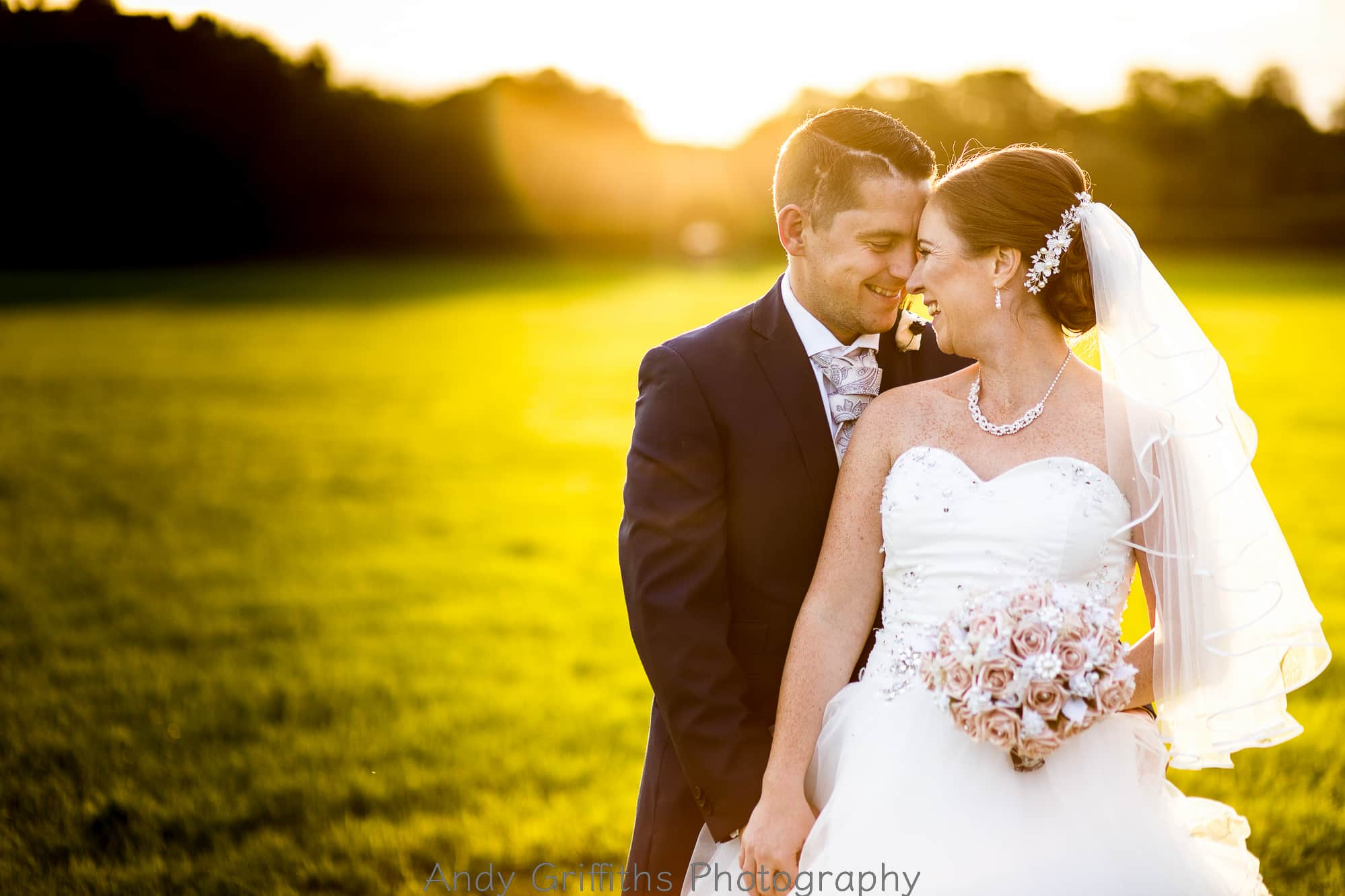 Bride and Groom cuddling and laughing in the sun