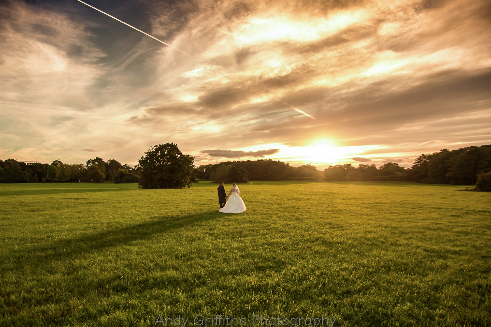 Bride and groom walking away into the sun