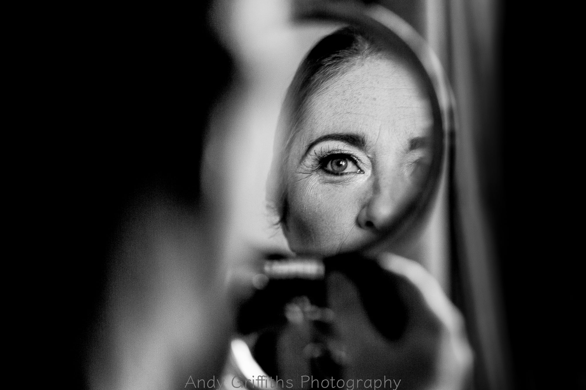 Bride having her make up done and is looking in the mirror