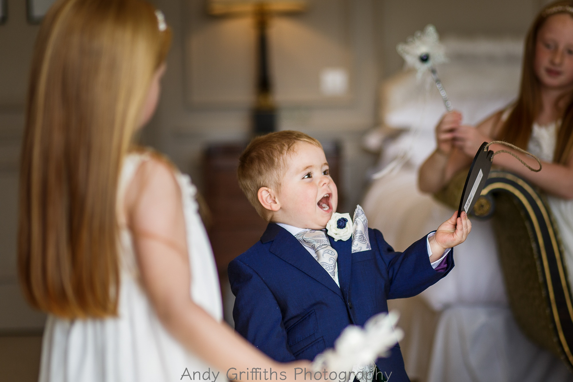 Page boy laughing with flower girls