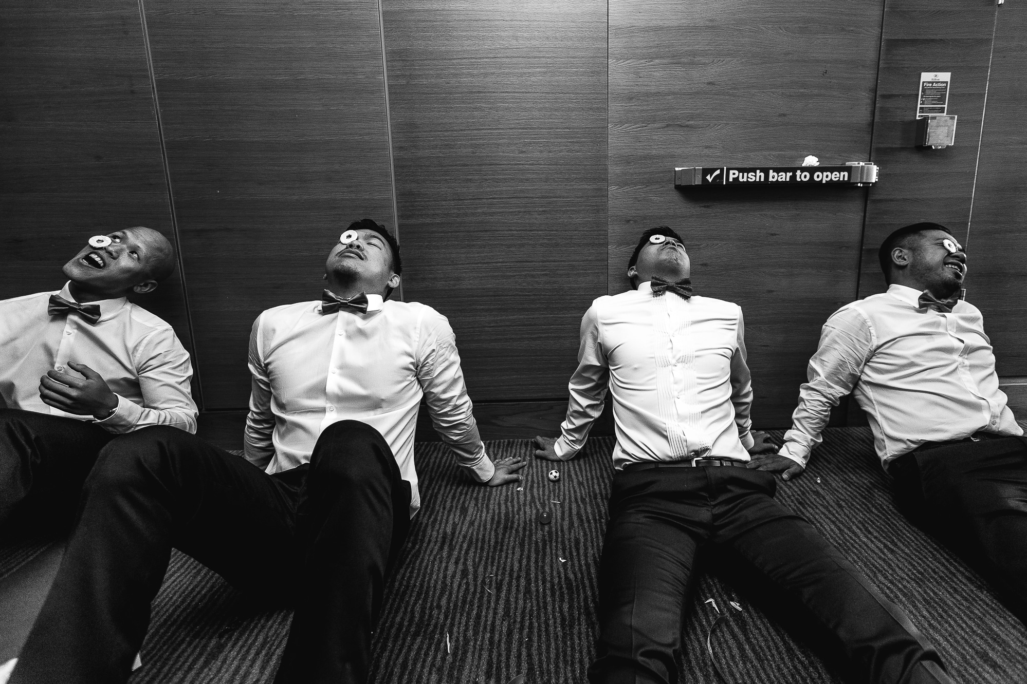 Groomsmen sitting on floor trying to complete a task at Hilton Manchester