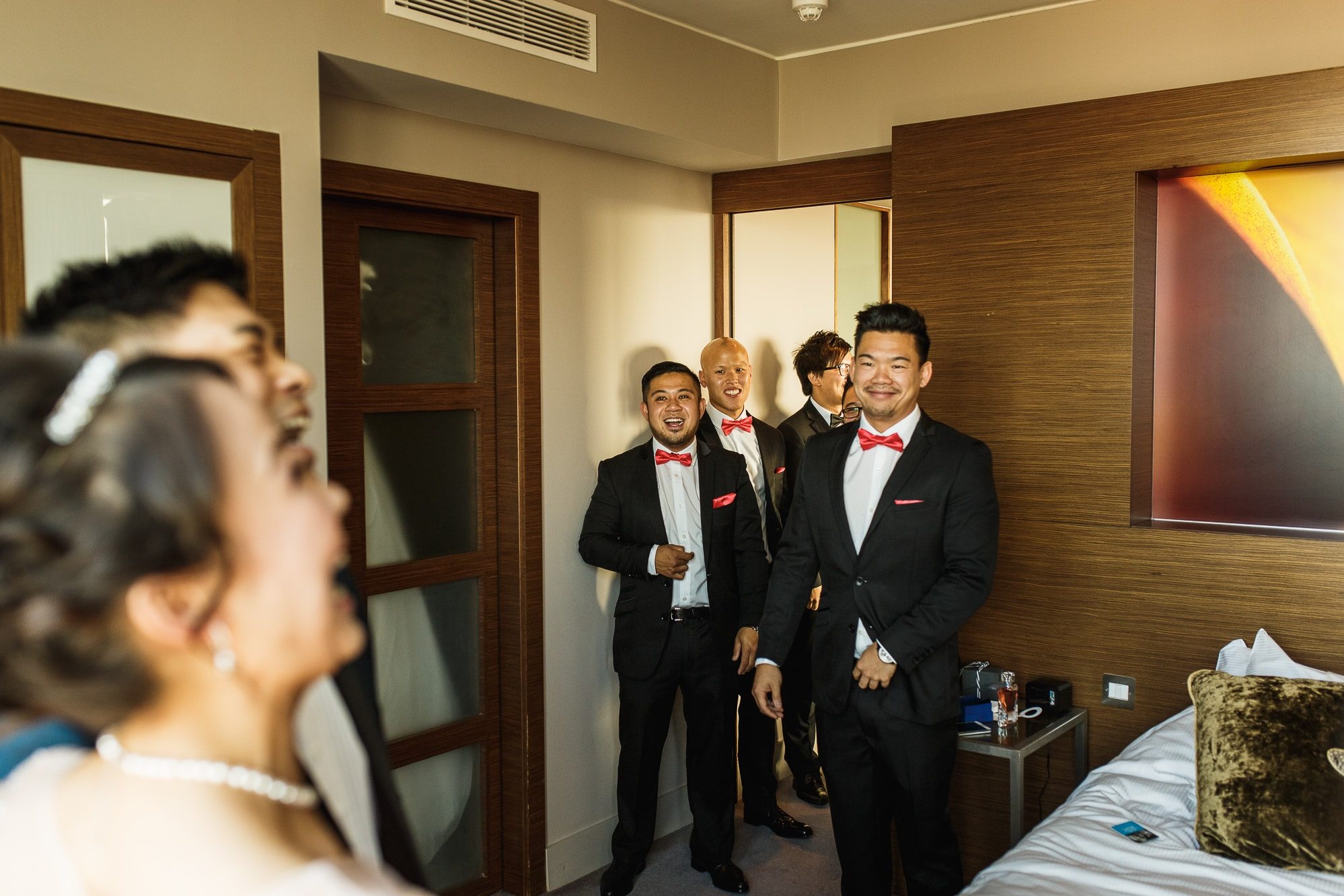 bride and groom laughing with ushers