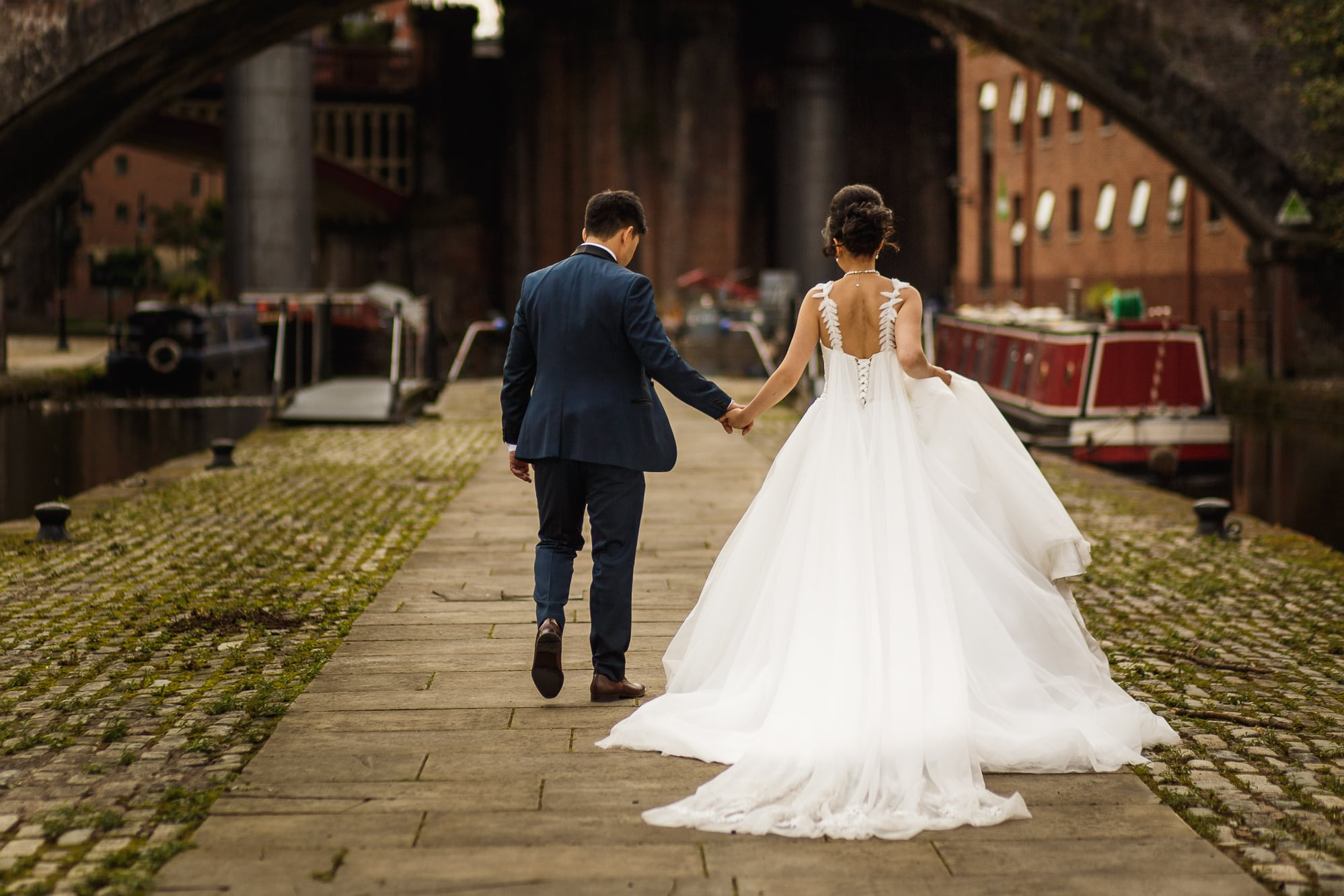 Bride and groom walking in Castlefield