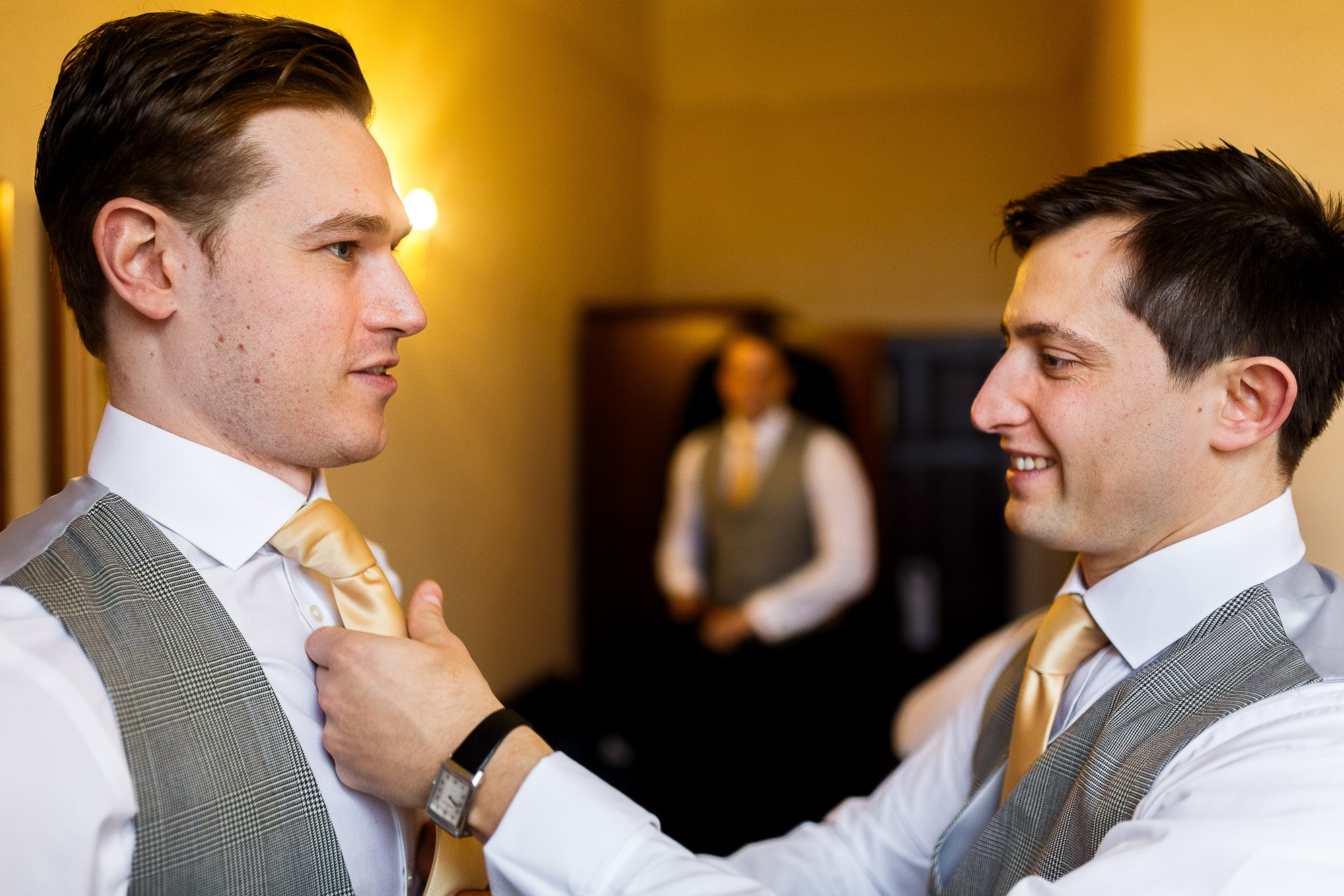 groom having his tie done up