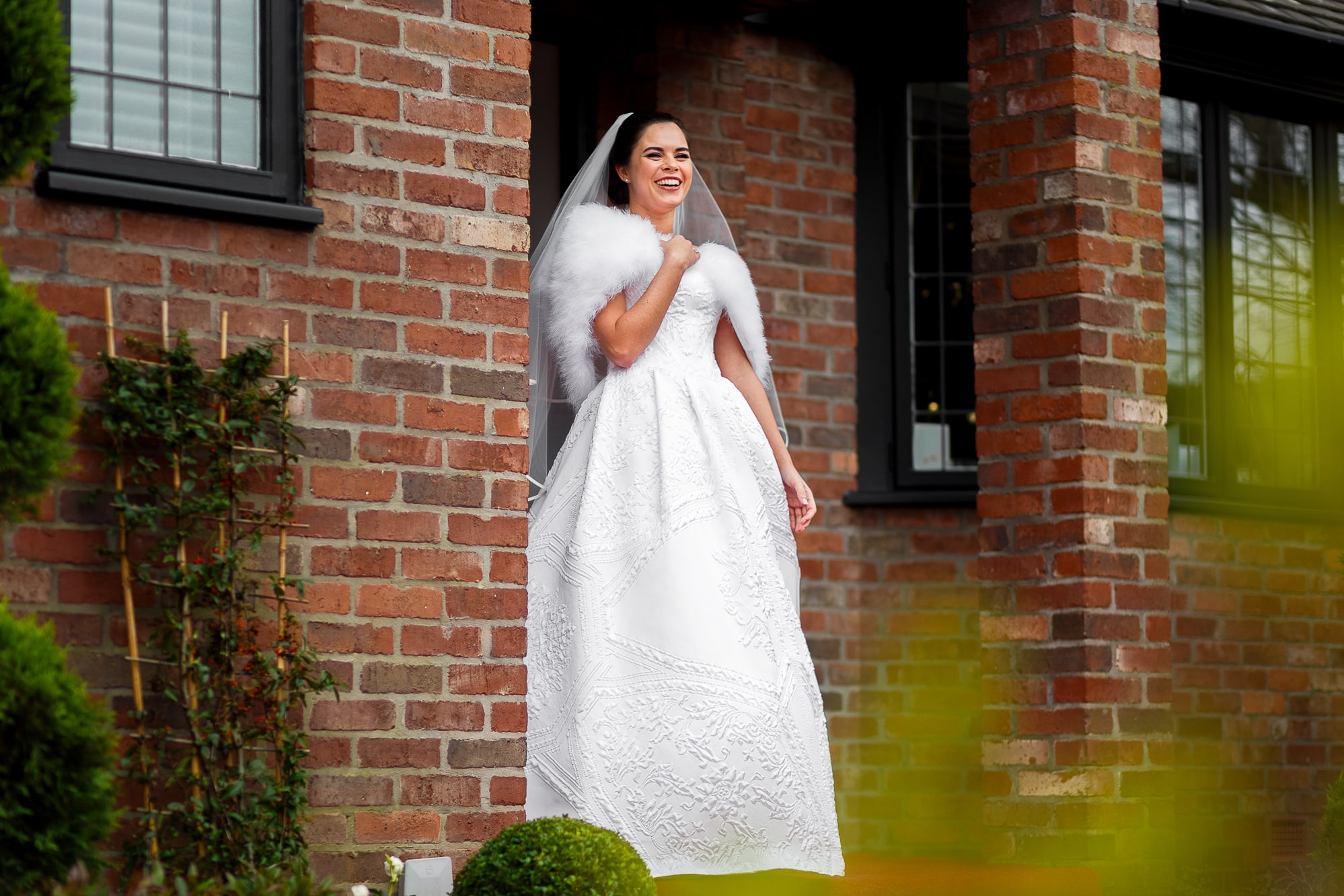bride laughing outside of house