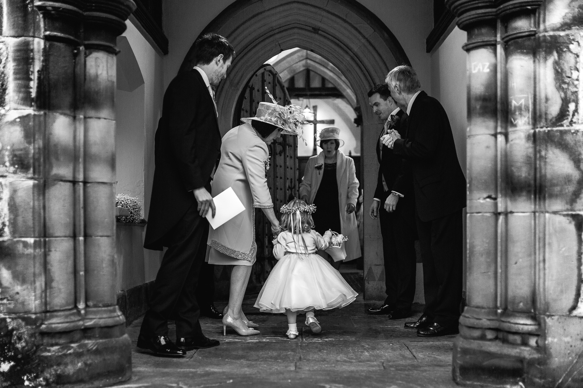 flower girl walking into church to be greeted by family