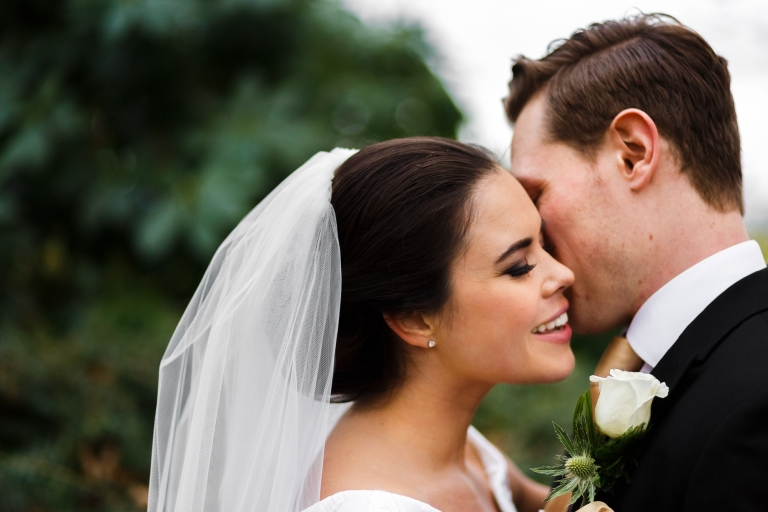 close up picture of groom whispering in brides ear