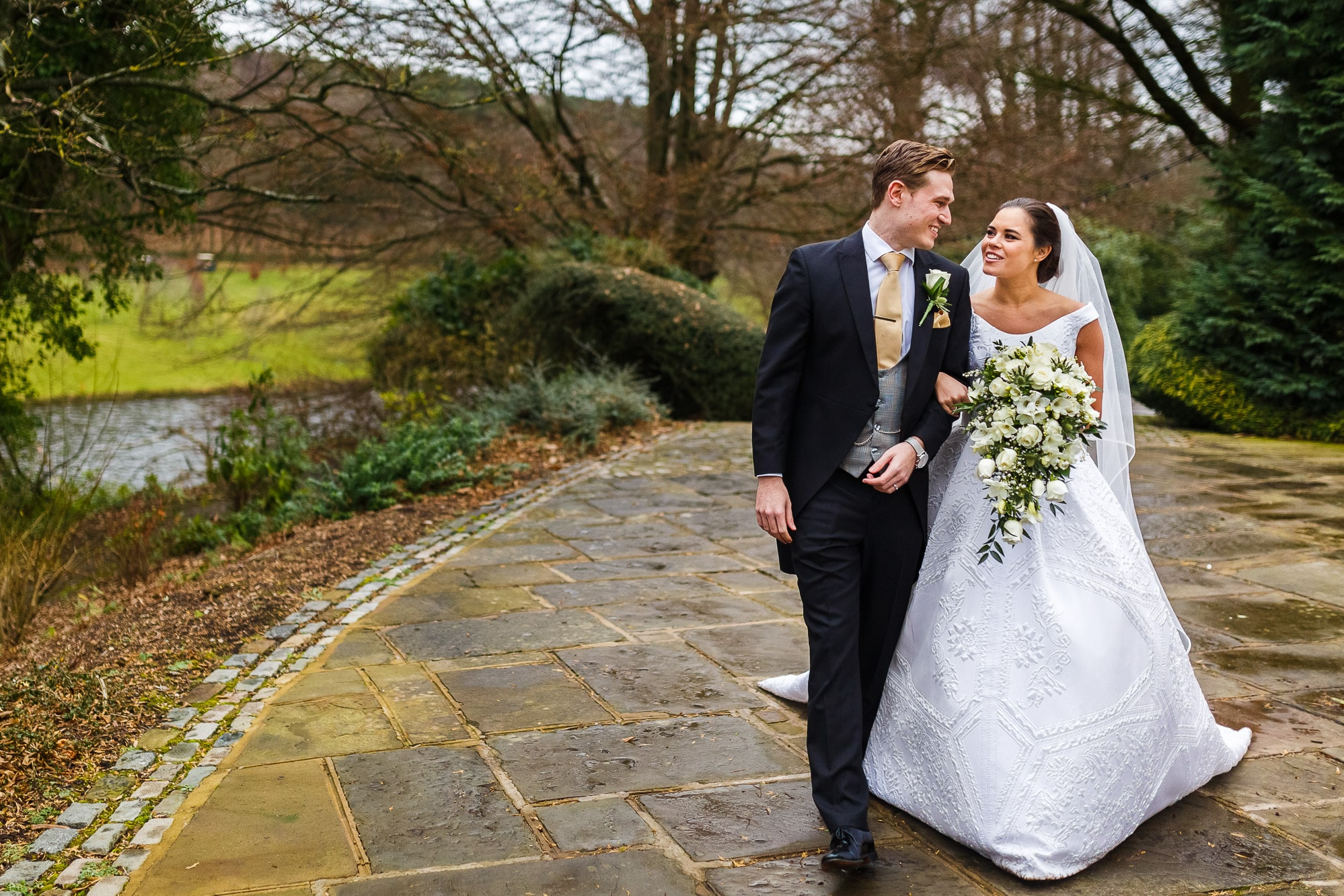 bride and groom walking with flowers through Shrigley Hall