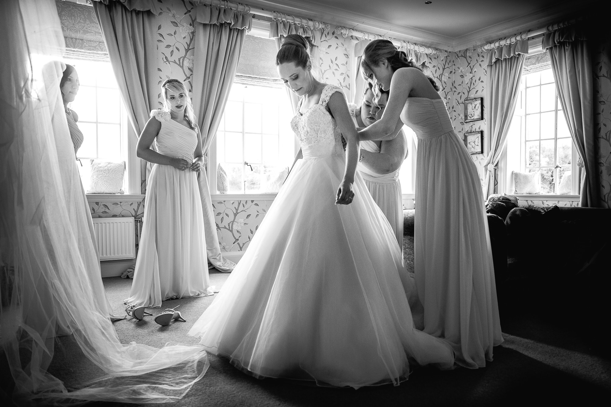 bride putting dress on with friends at Eaves Hall