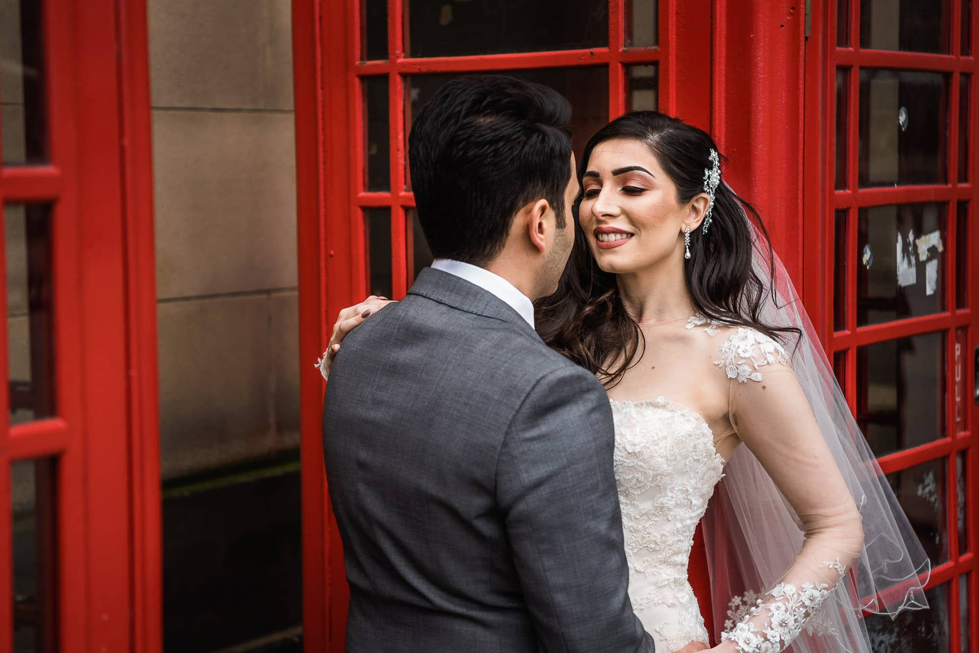 Bride and groom against phone box