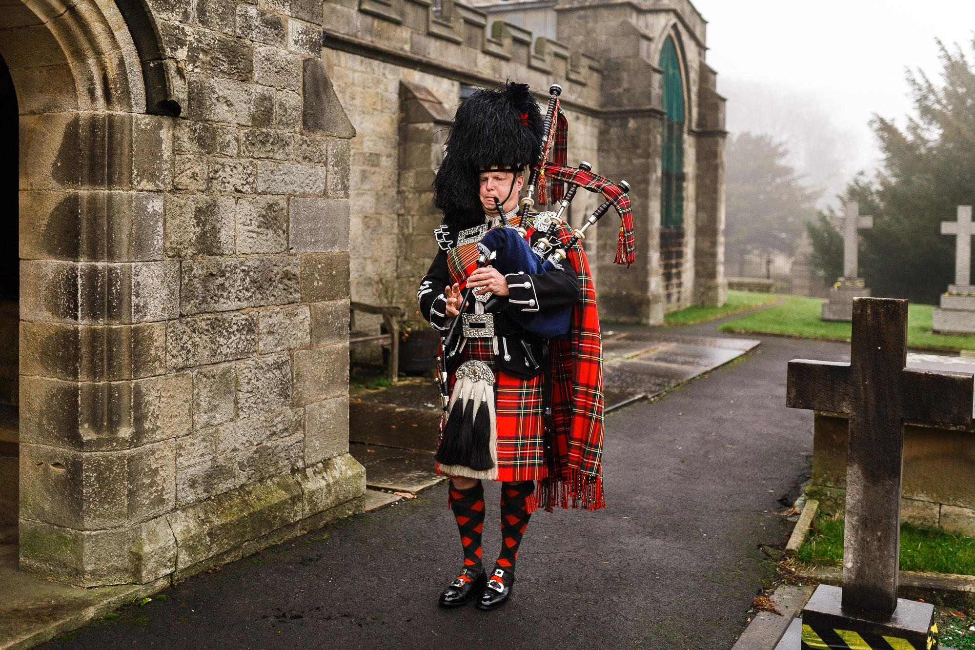 Scots guard bagpiper outside the church