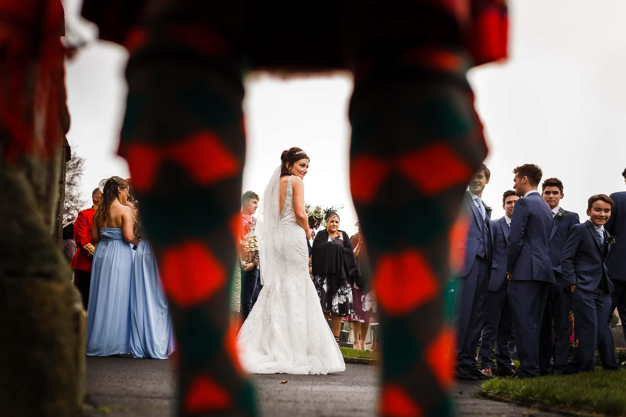 bride shot through bagpipers legs