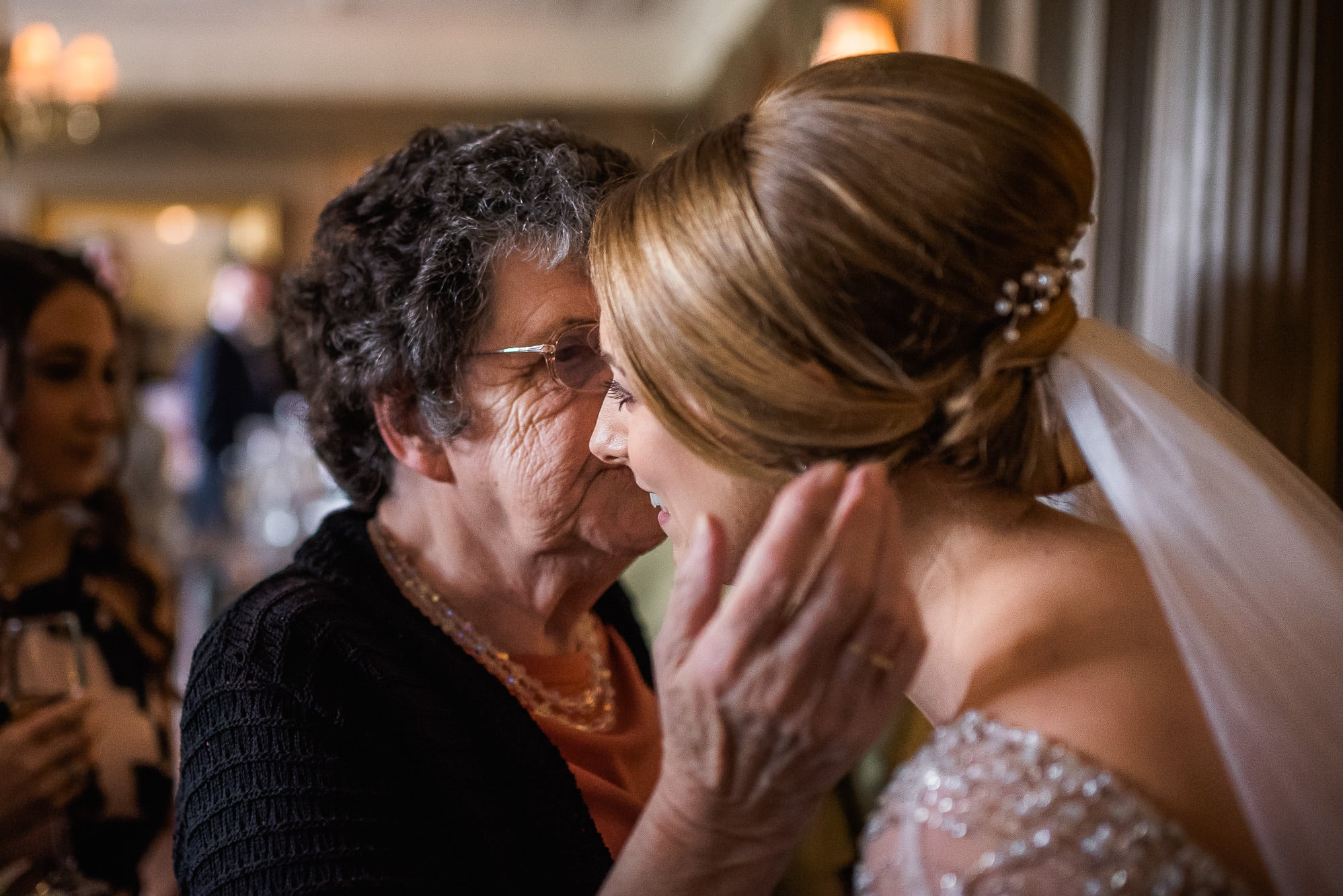 Bride being hugged by guest