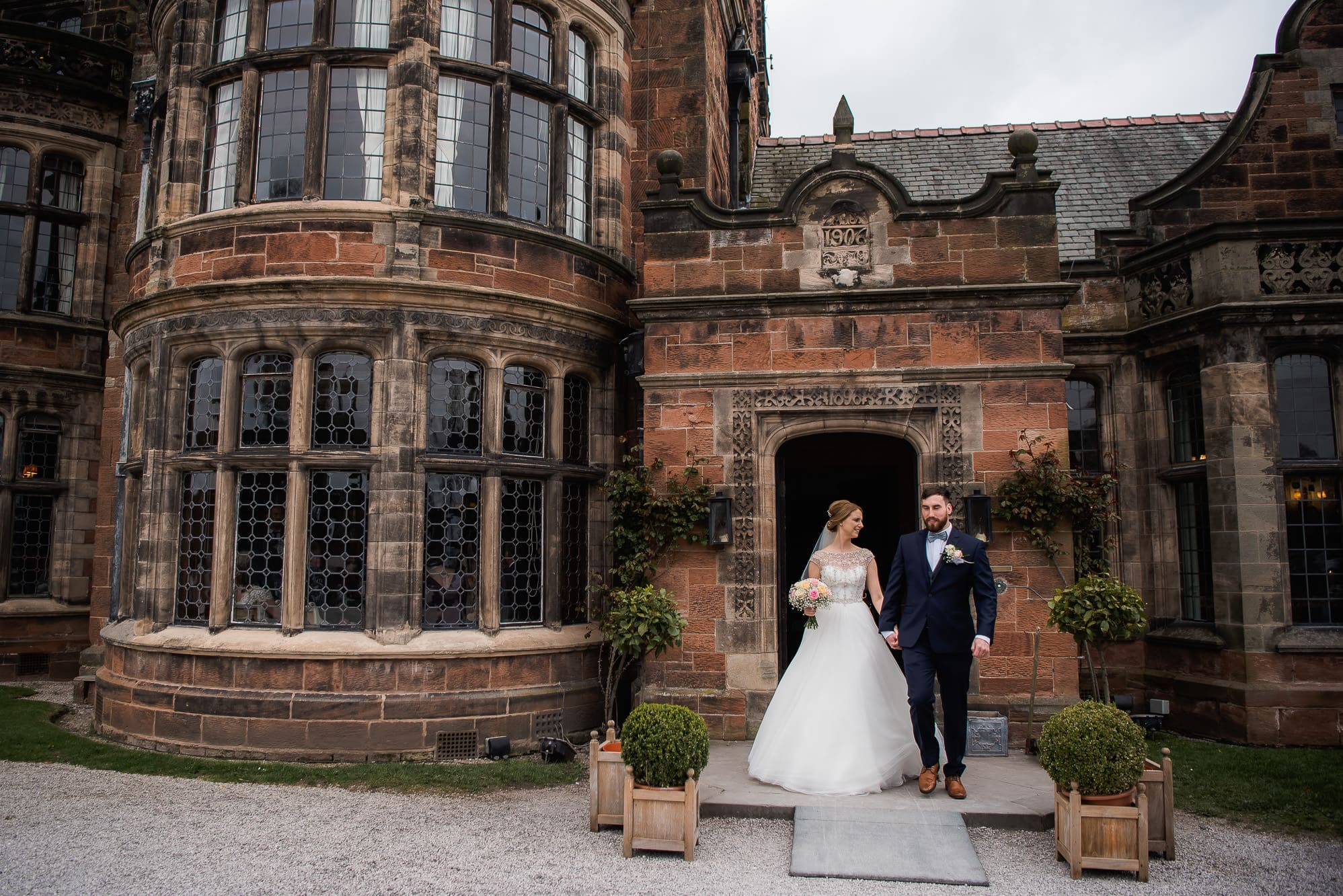 Bride and groom walking out of Thornton Manor