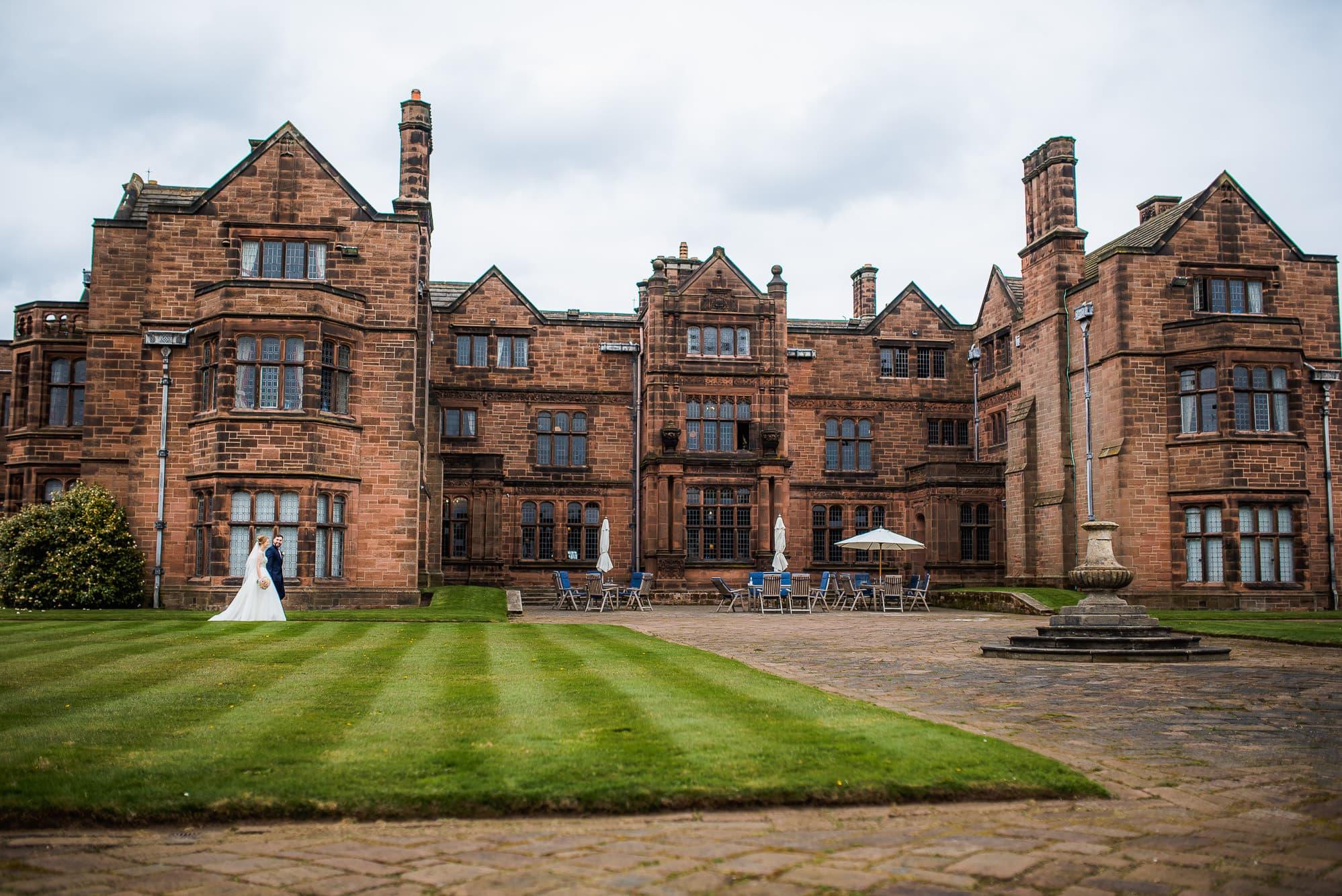 bride and groom walking by Thornton Manor
