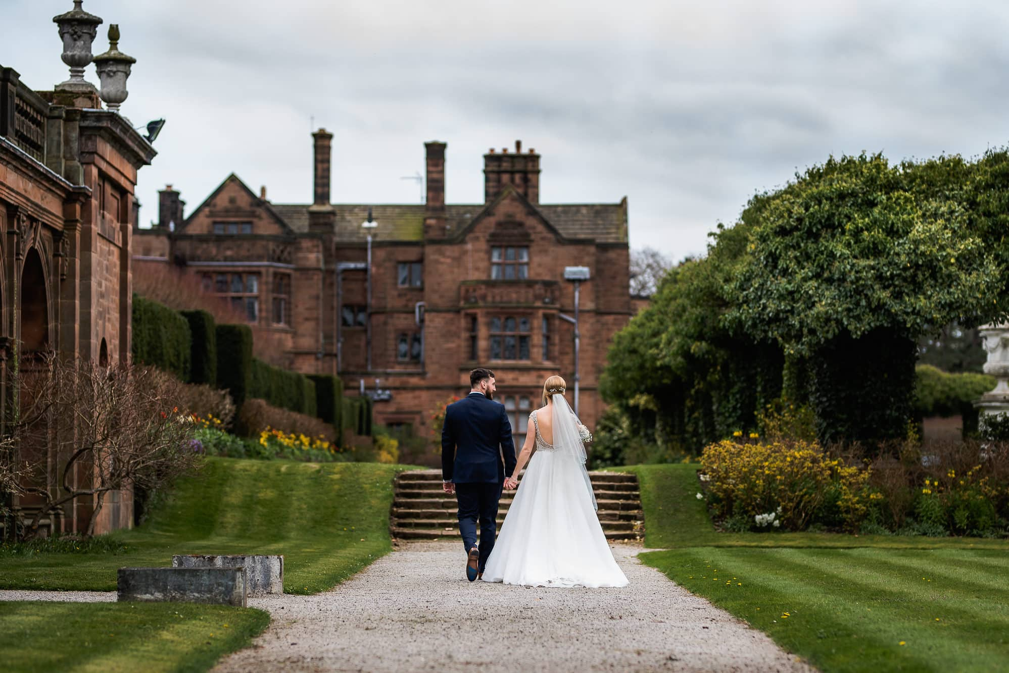 Bride and groom walking towards the manor