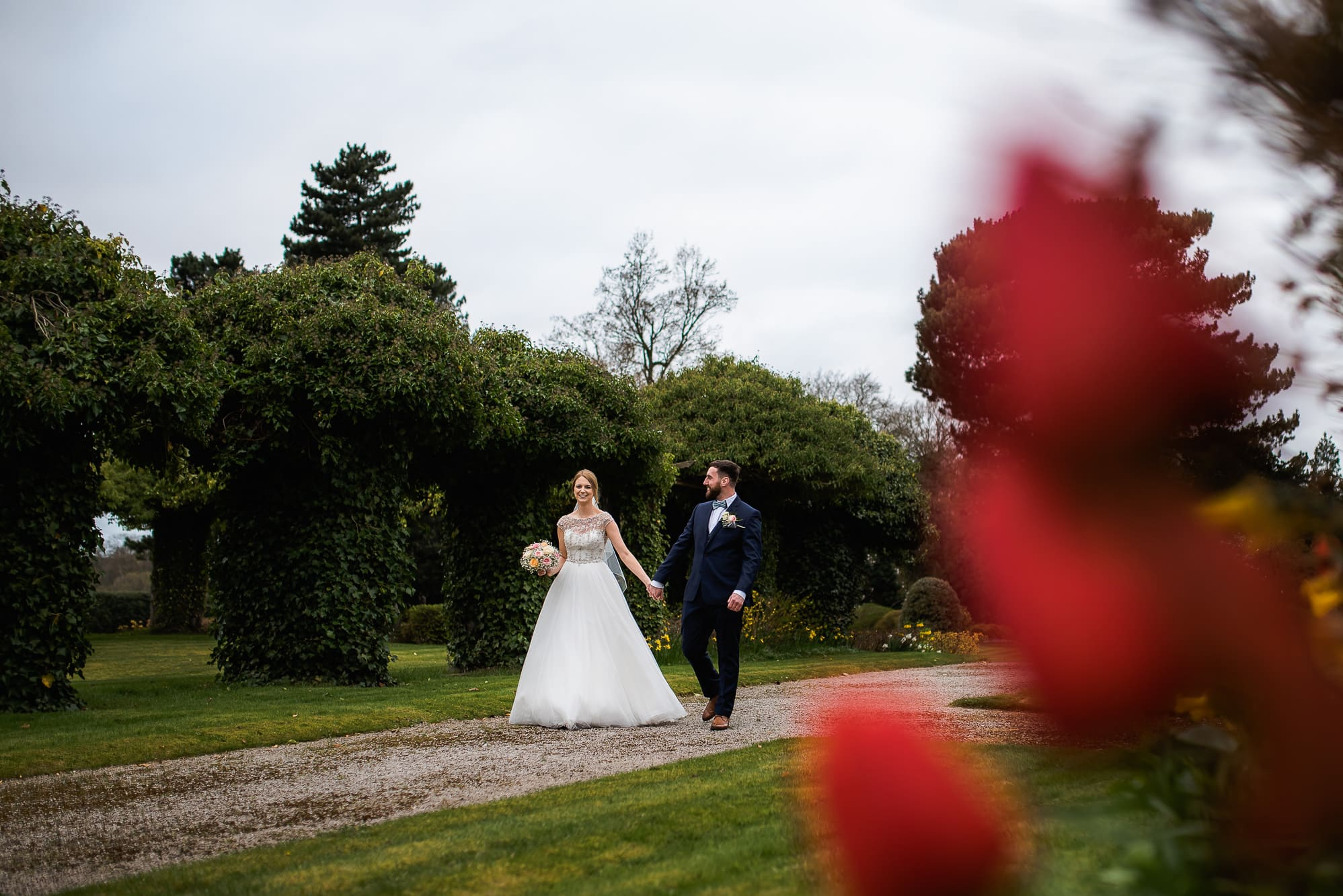 bride and groom walking with flowers