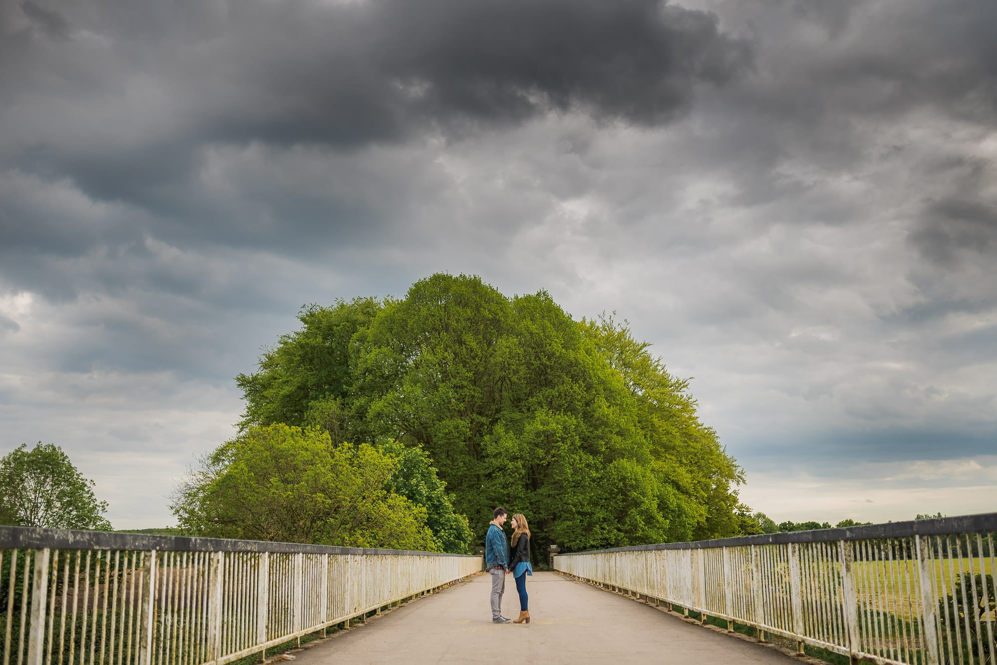 bride and groom standing on a bridge cuddling