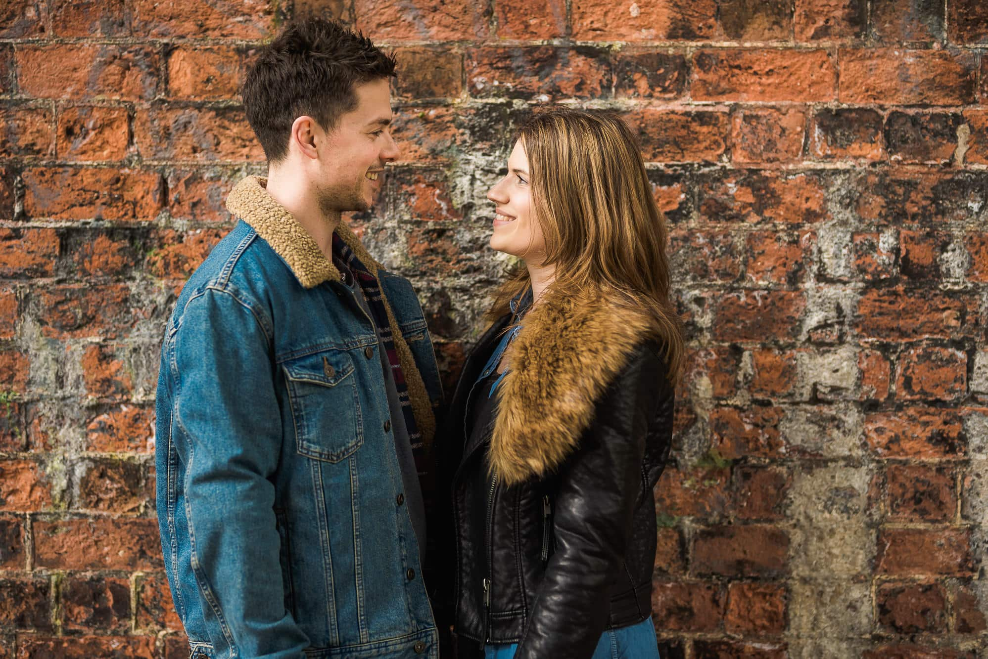 Couple smiling against a wall in Avenham Park