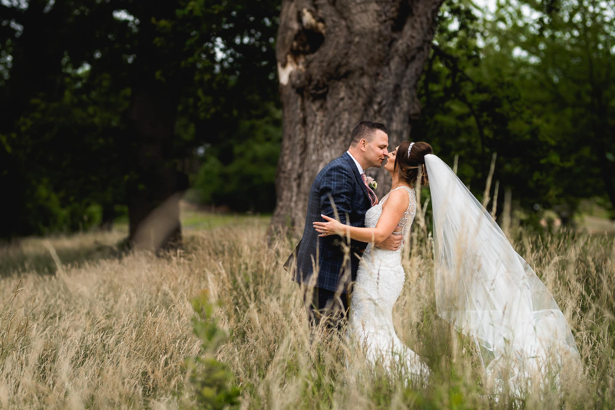 Bride and groom kissing in the field