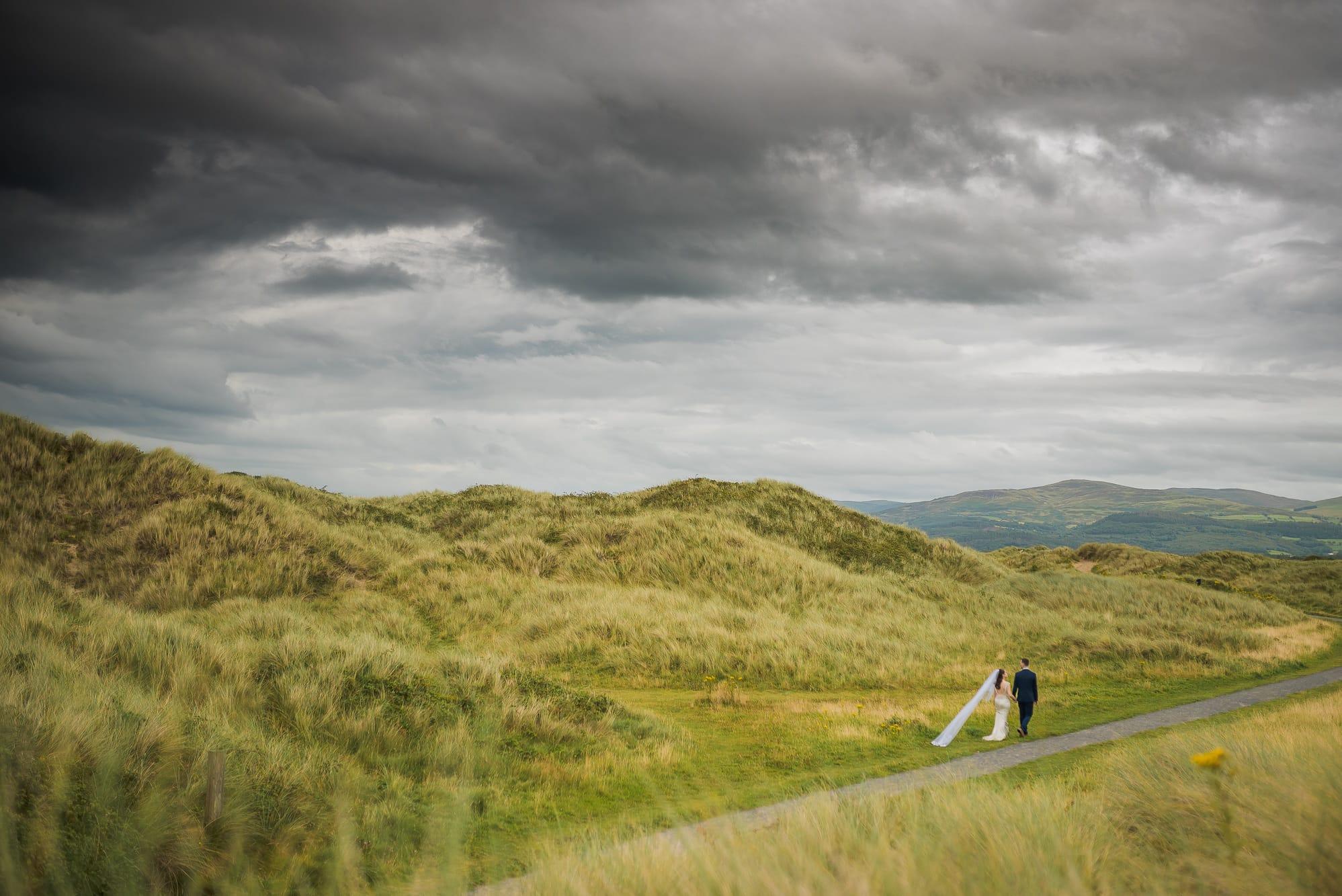 Bride and groom walking in Ynyslas