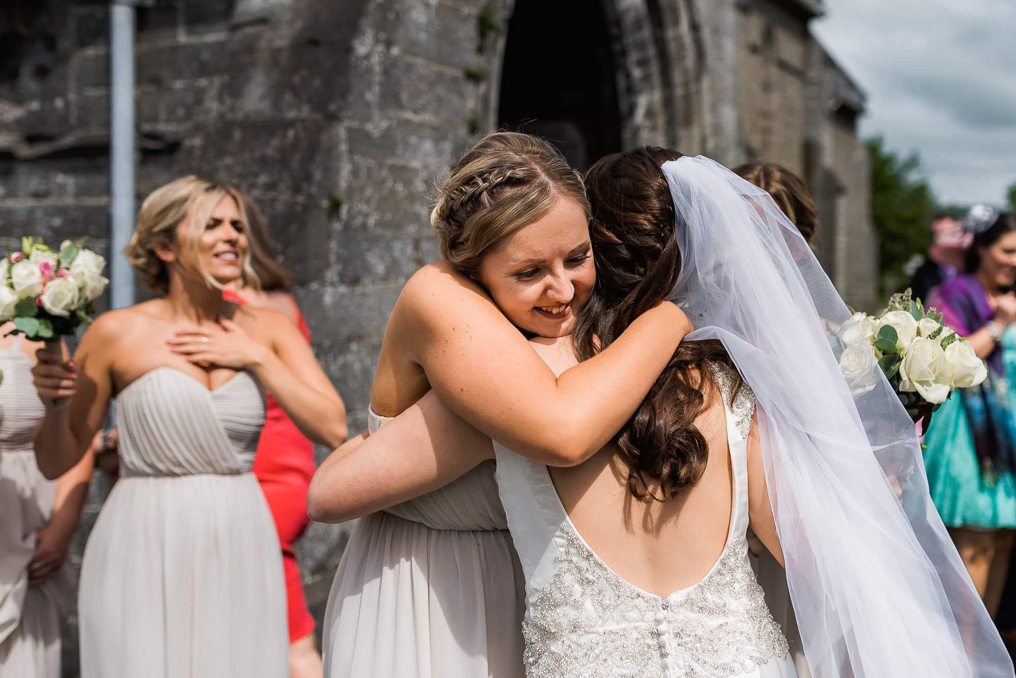 bridesmaid hugging bride outside church