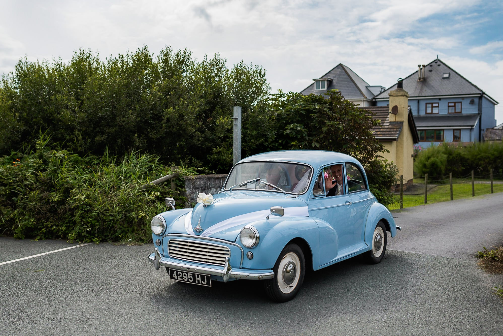 couple arriving in blue wedding car