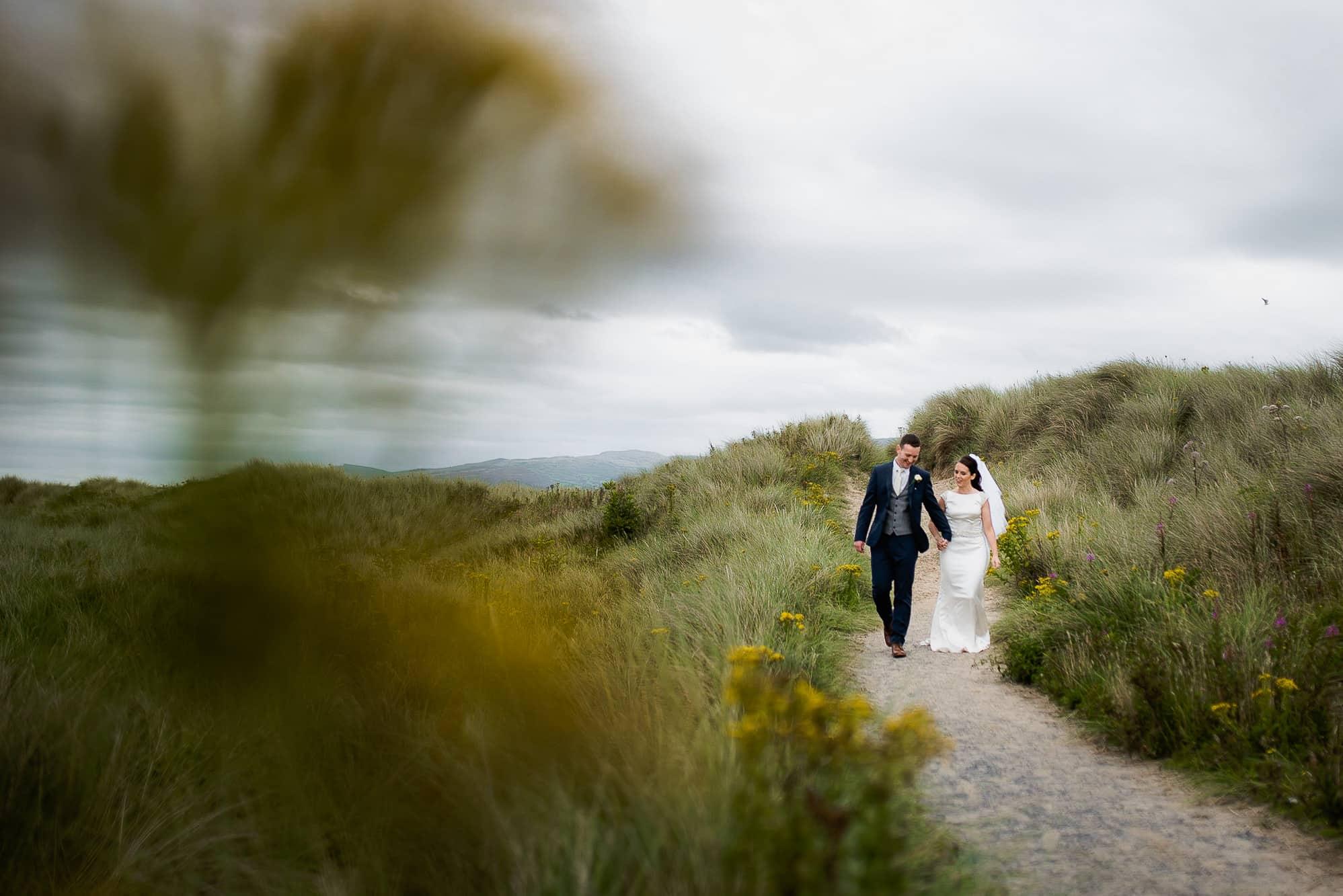 couple walking on a path on their wedding day in Ynyslas, Aberystwyth