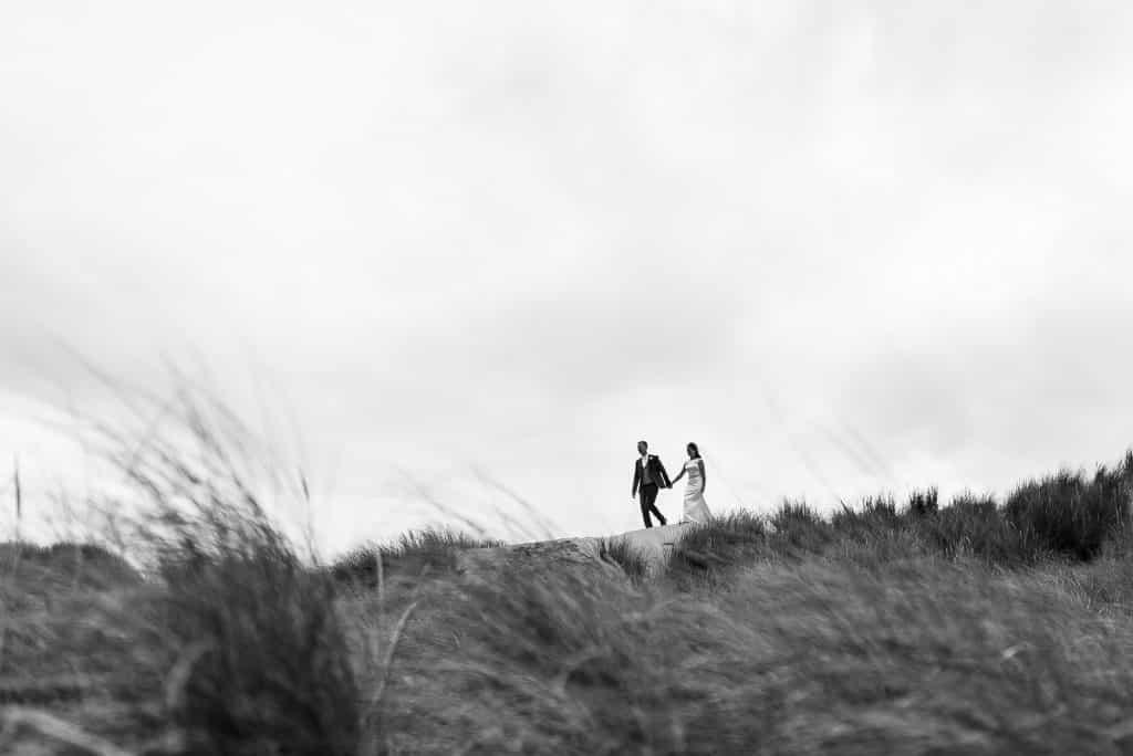 couple walking on top of sand dunes