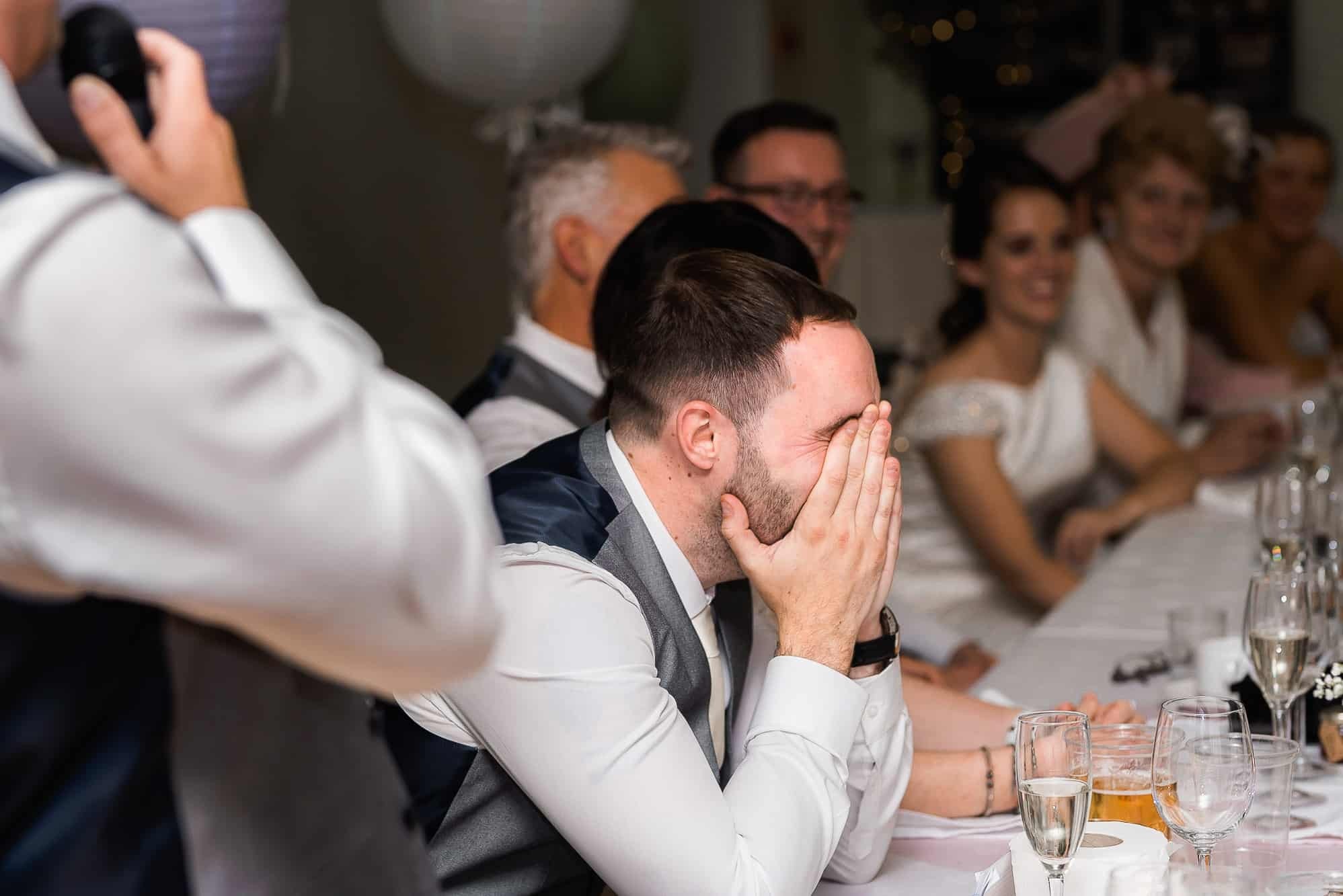 best man laughing with head in hands