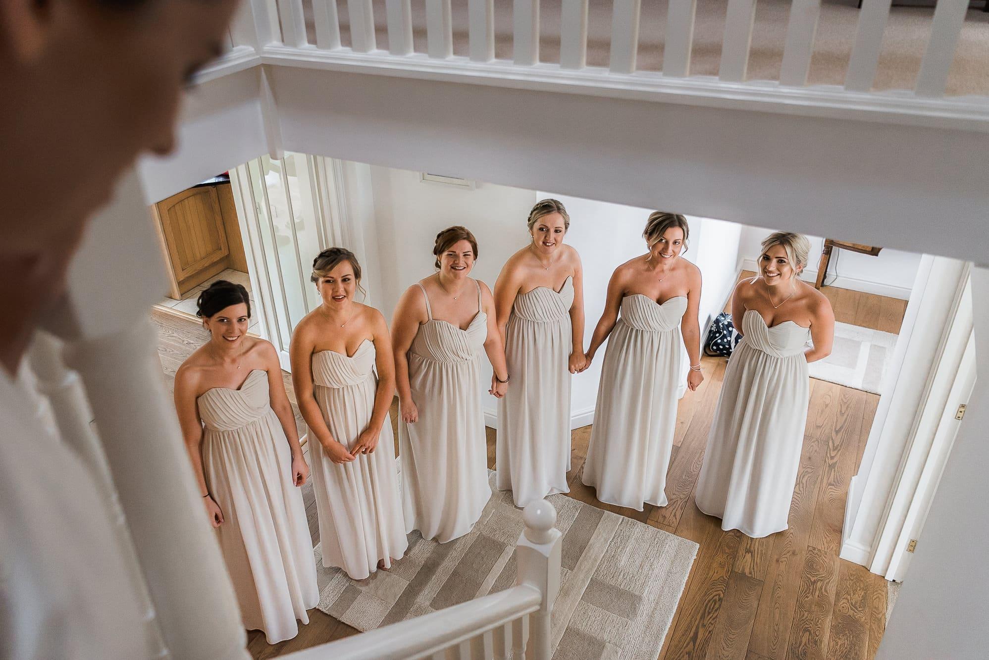 bridesmaids waiting for bride walking down the sairs
