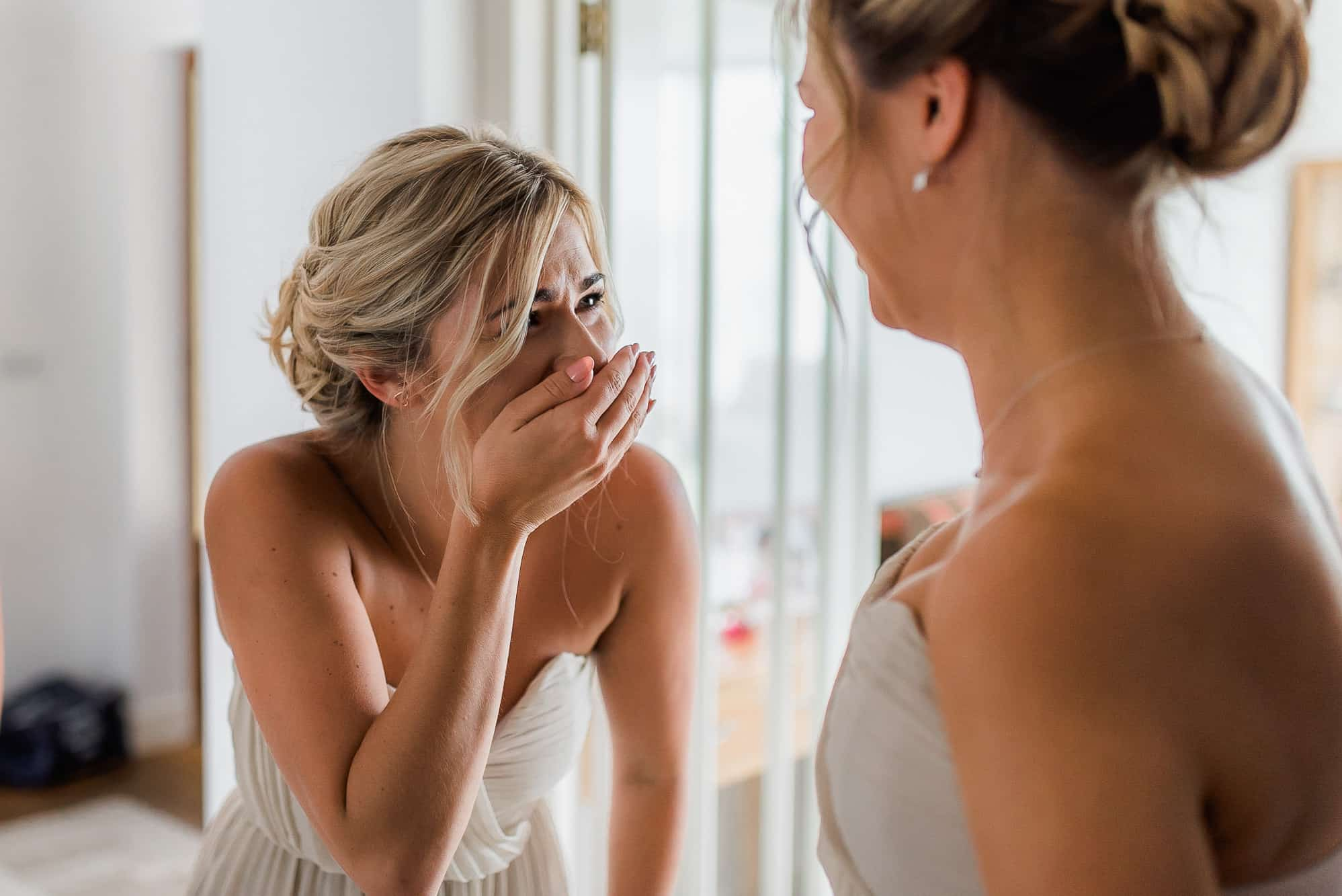 bridesmaid crying after seeing bride in dress