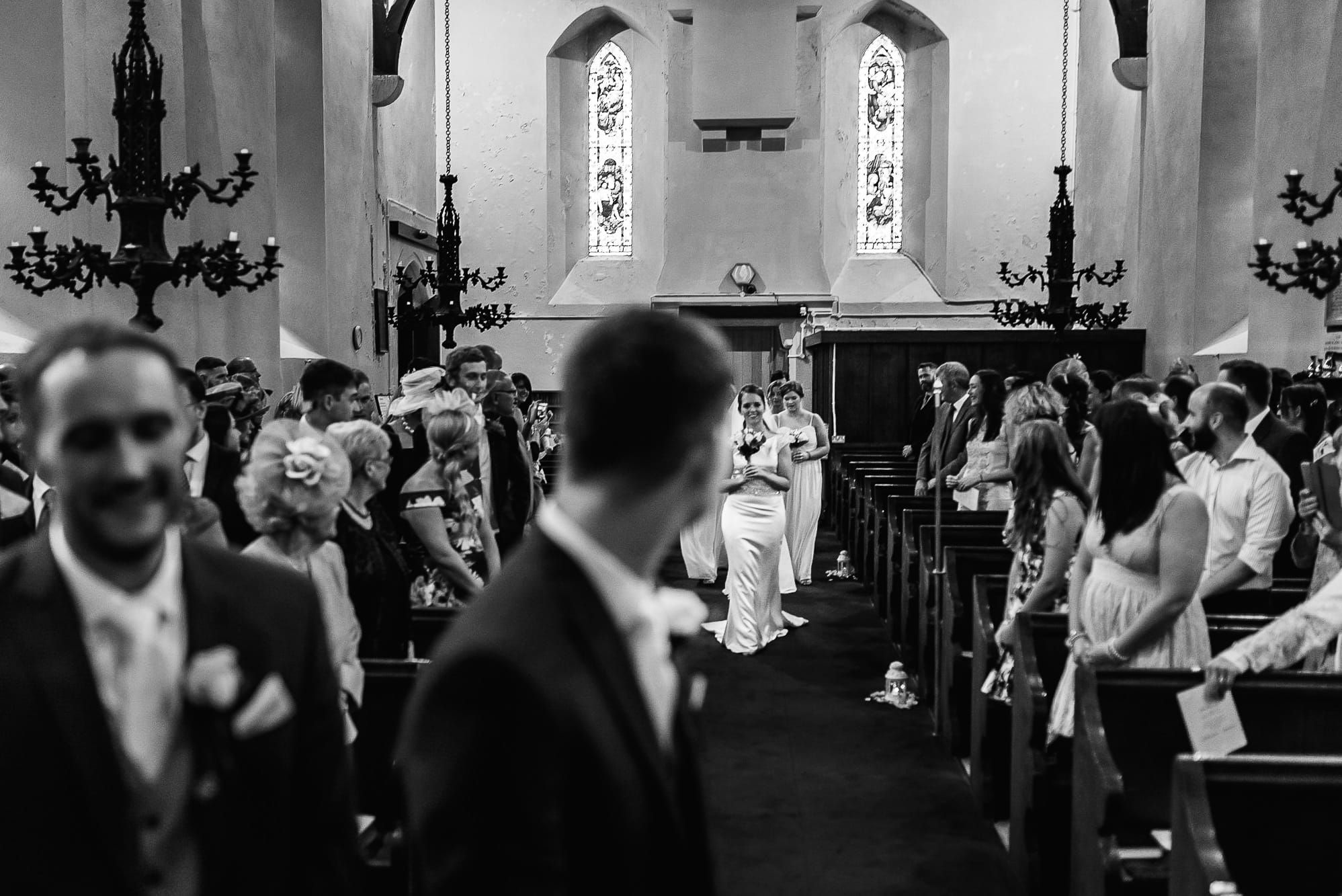 groom looking down the aisle at his wife