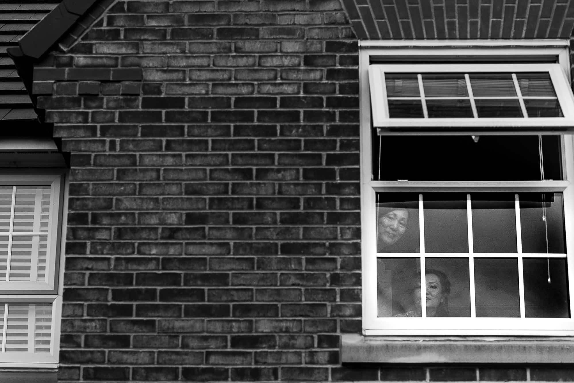Bride looking on from window