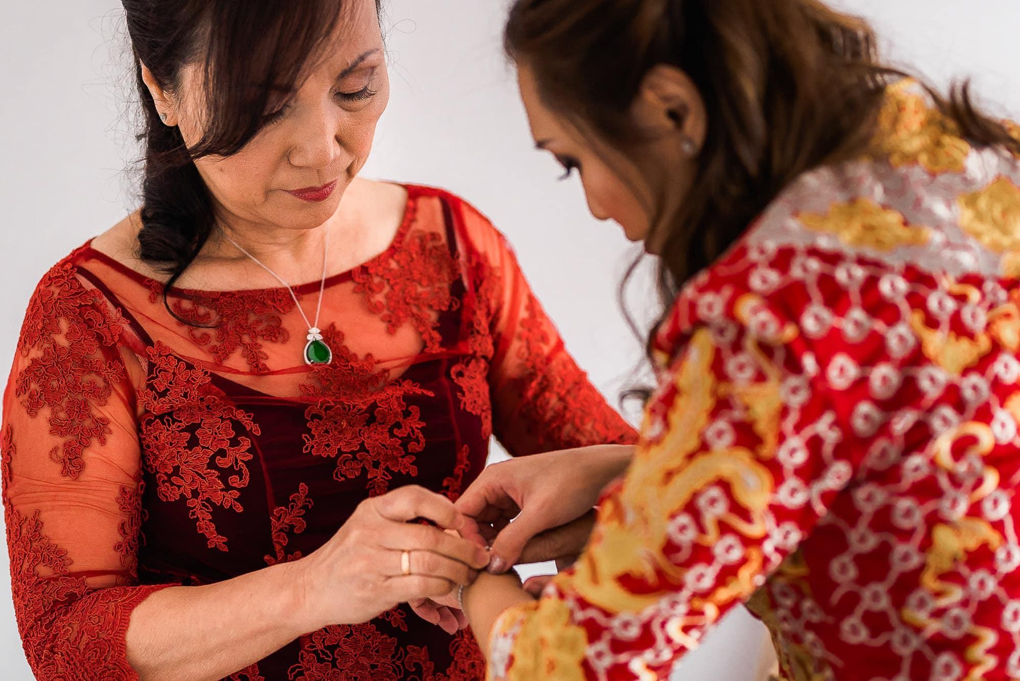 Mum helping bride into dress