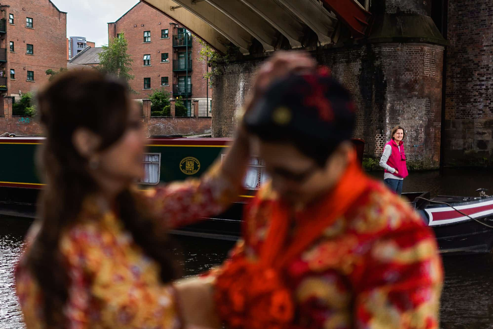 Canal boat going past bride and groom