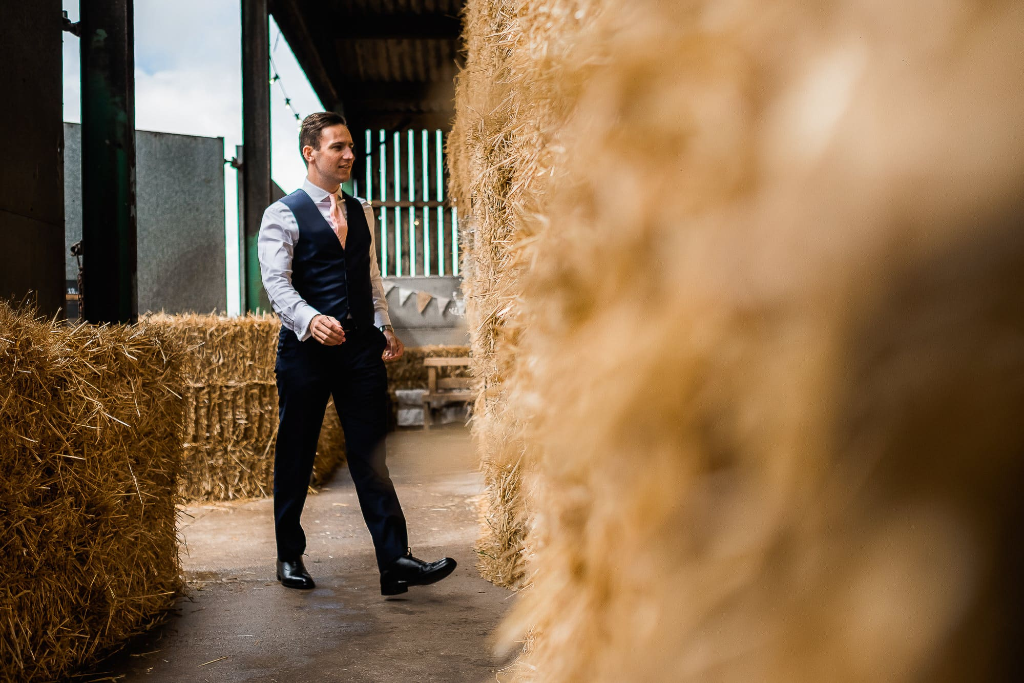 best man walking past some hay