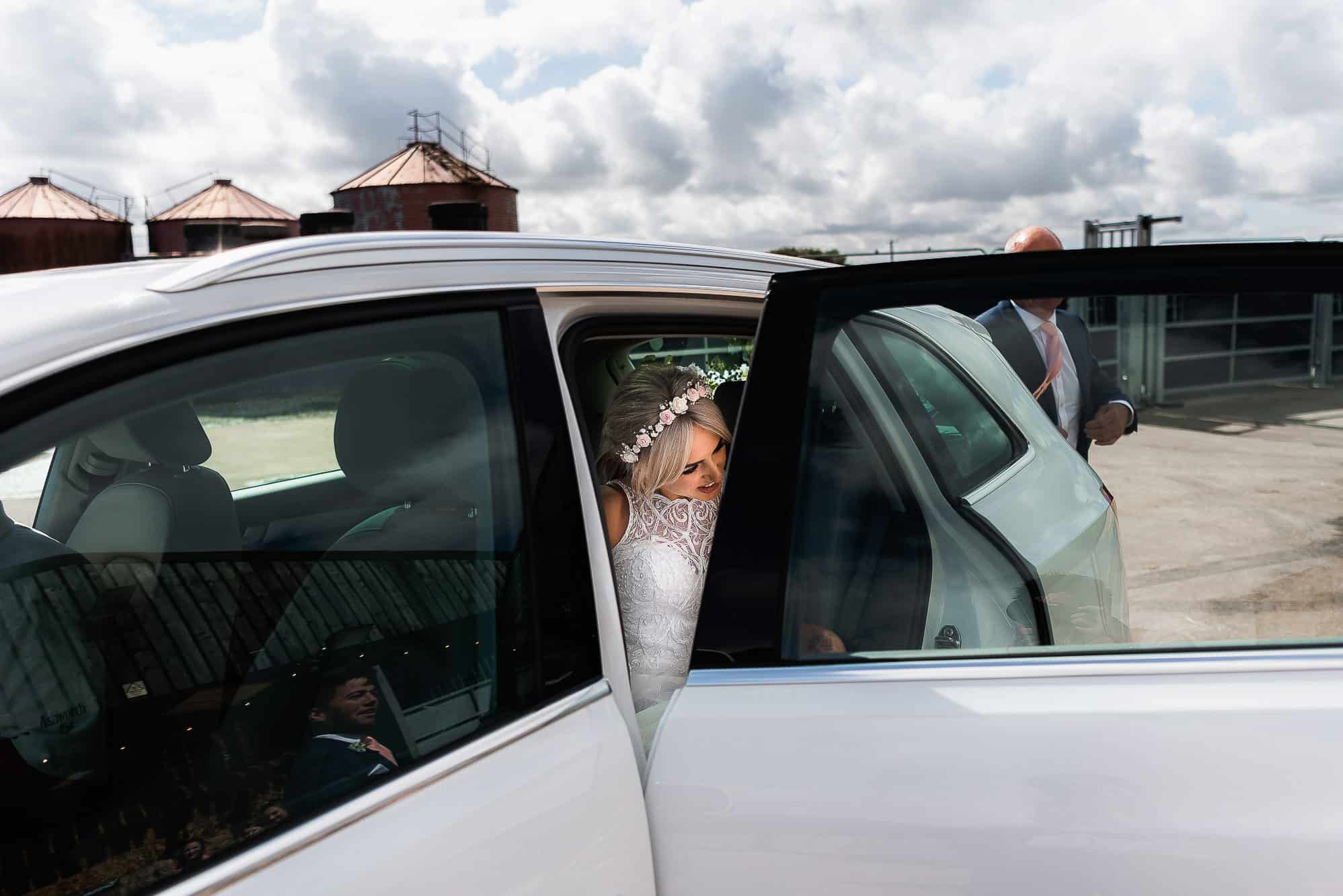 Bride getting out of car at the farm