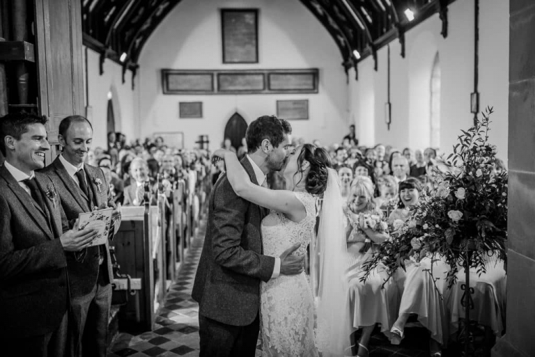 First kiss between the bride and groom at a marquee wedding