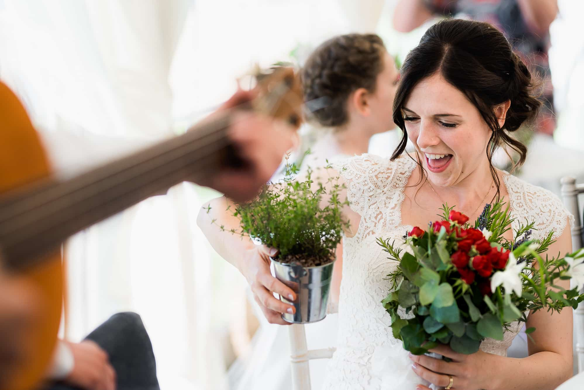 Bride laughing holding plant pots