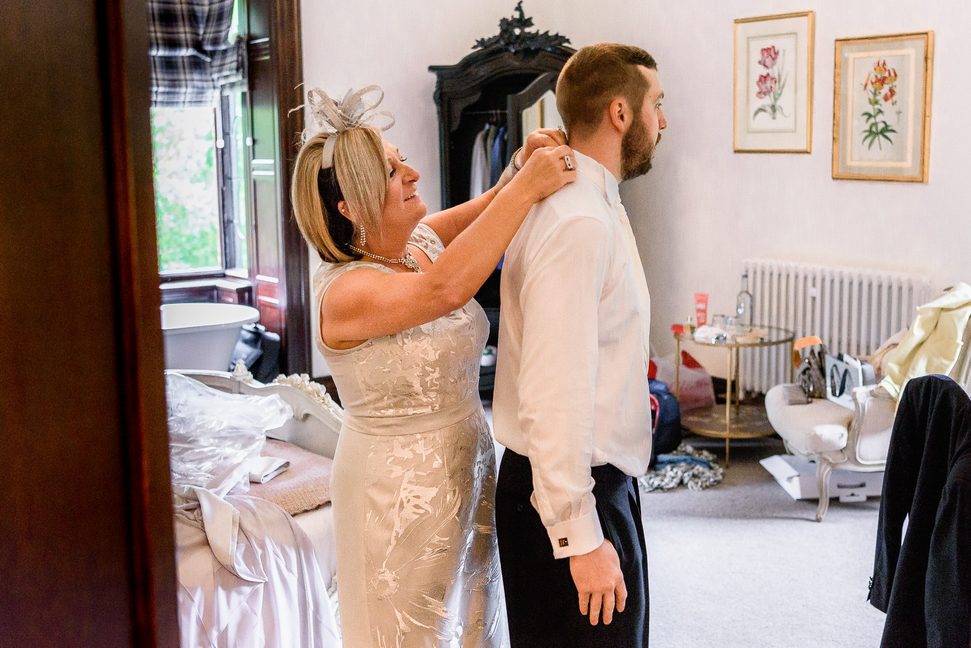 Grooms mum helping groom get dressed