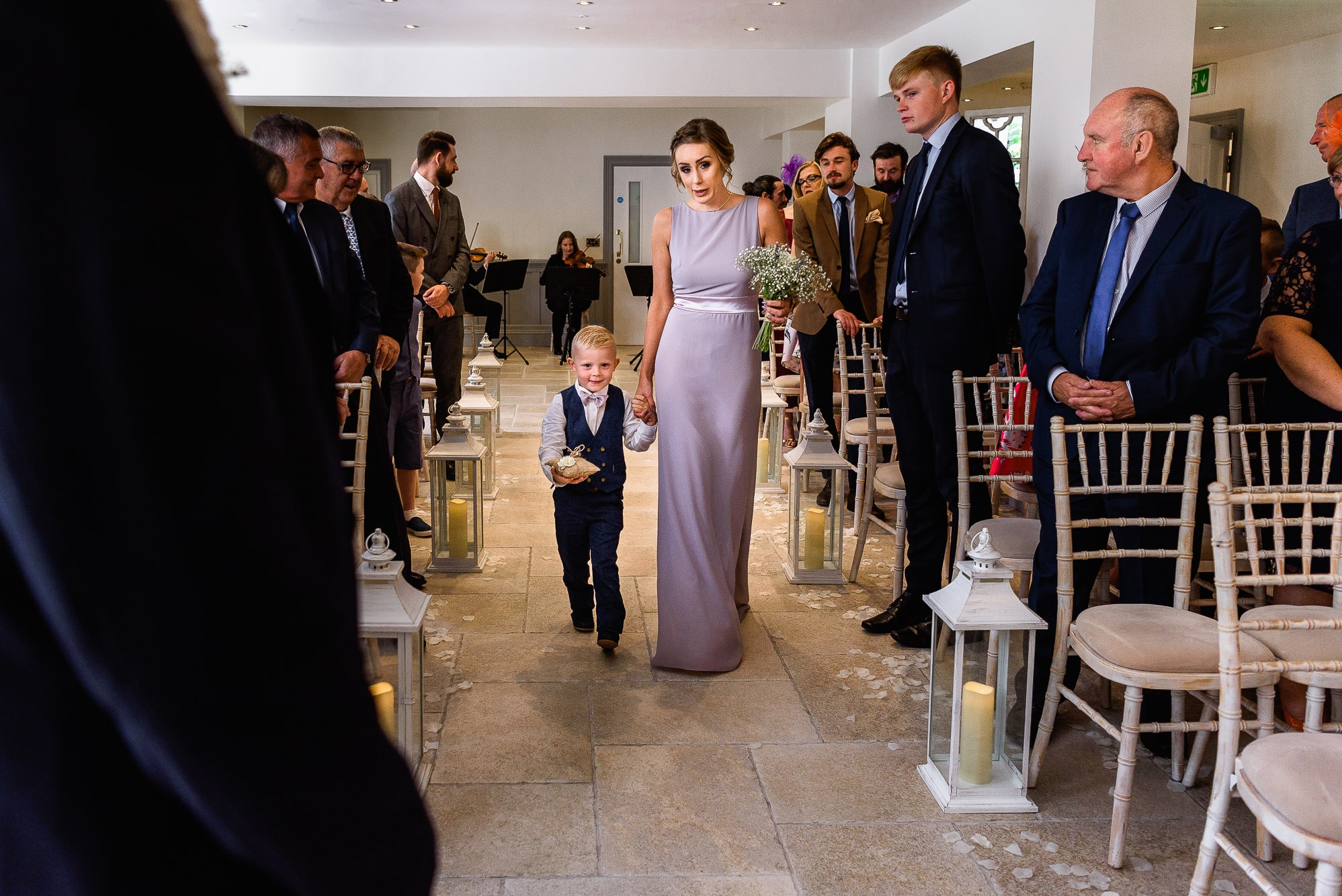 Bridesmaid walking down aisle with page boy