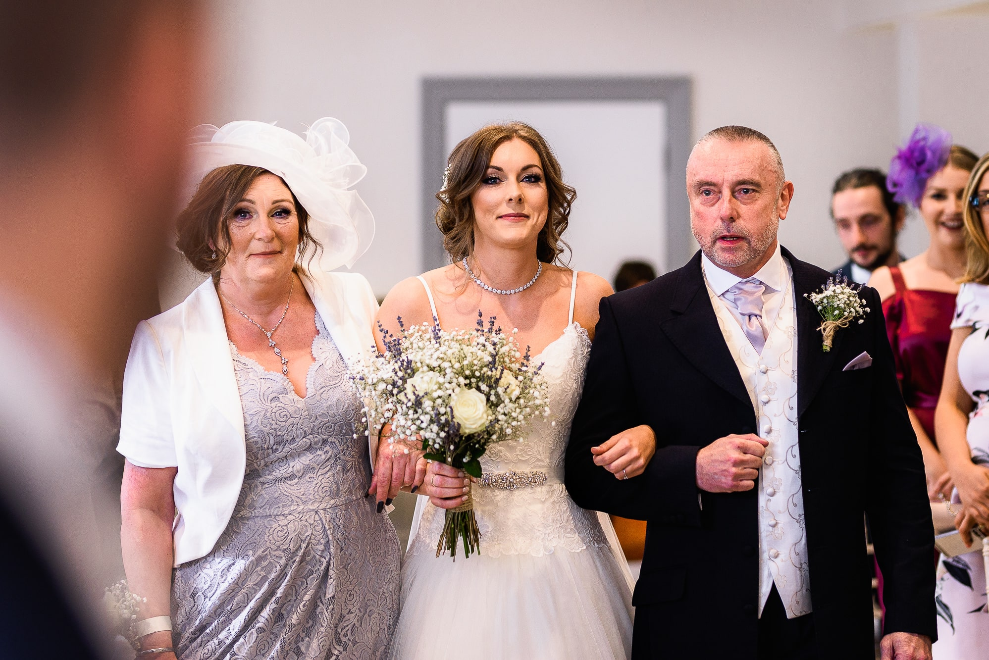 Bride walking down the aisle with her parents