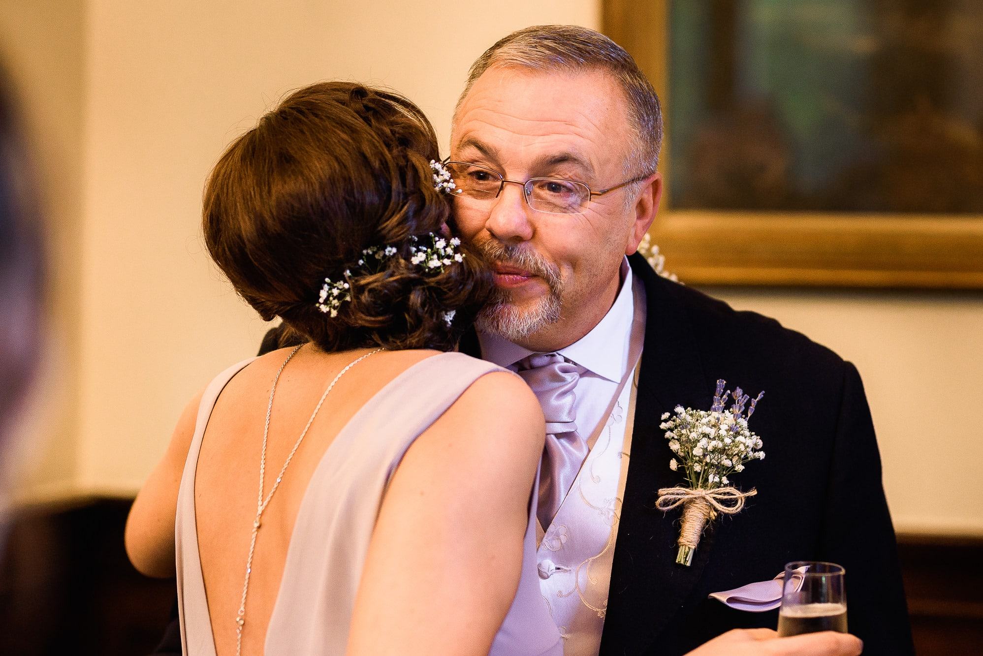 Father of bride and bridesmaid kissing