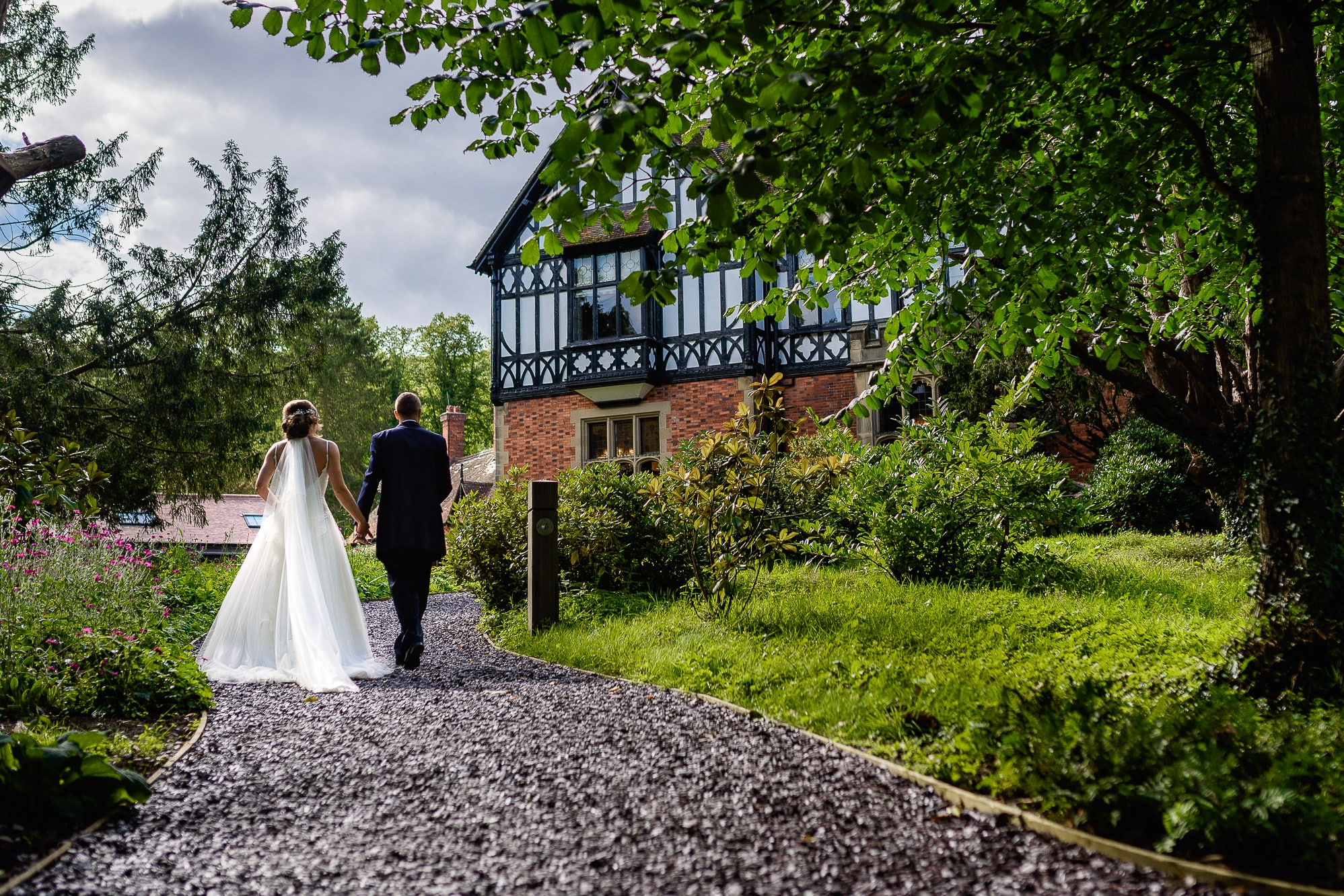 Bride and Groom walking to Tyn Dwr Hall