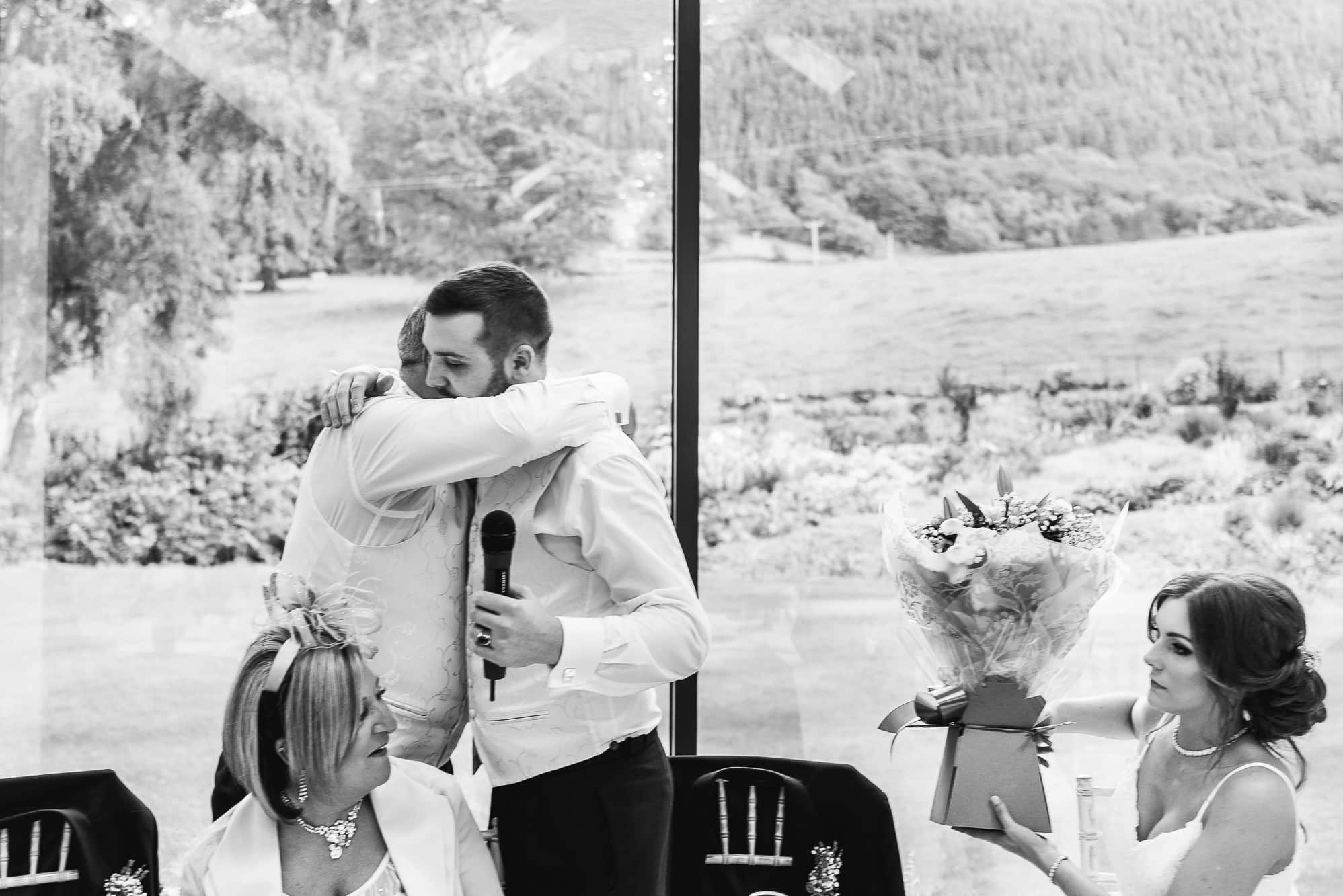 Groom and his dad hugging during wedding speeches