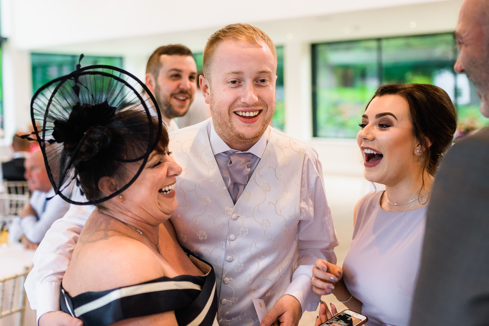 Guests laughing during reception drinks at Tyn Dwr Hall