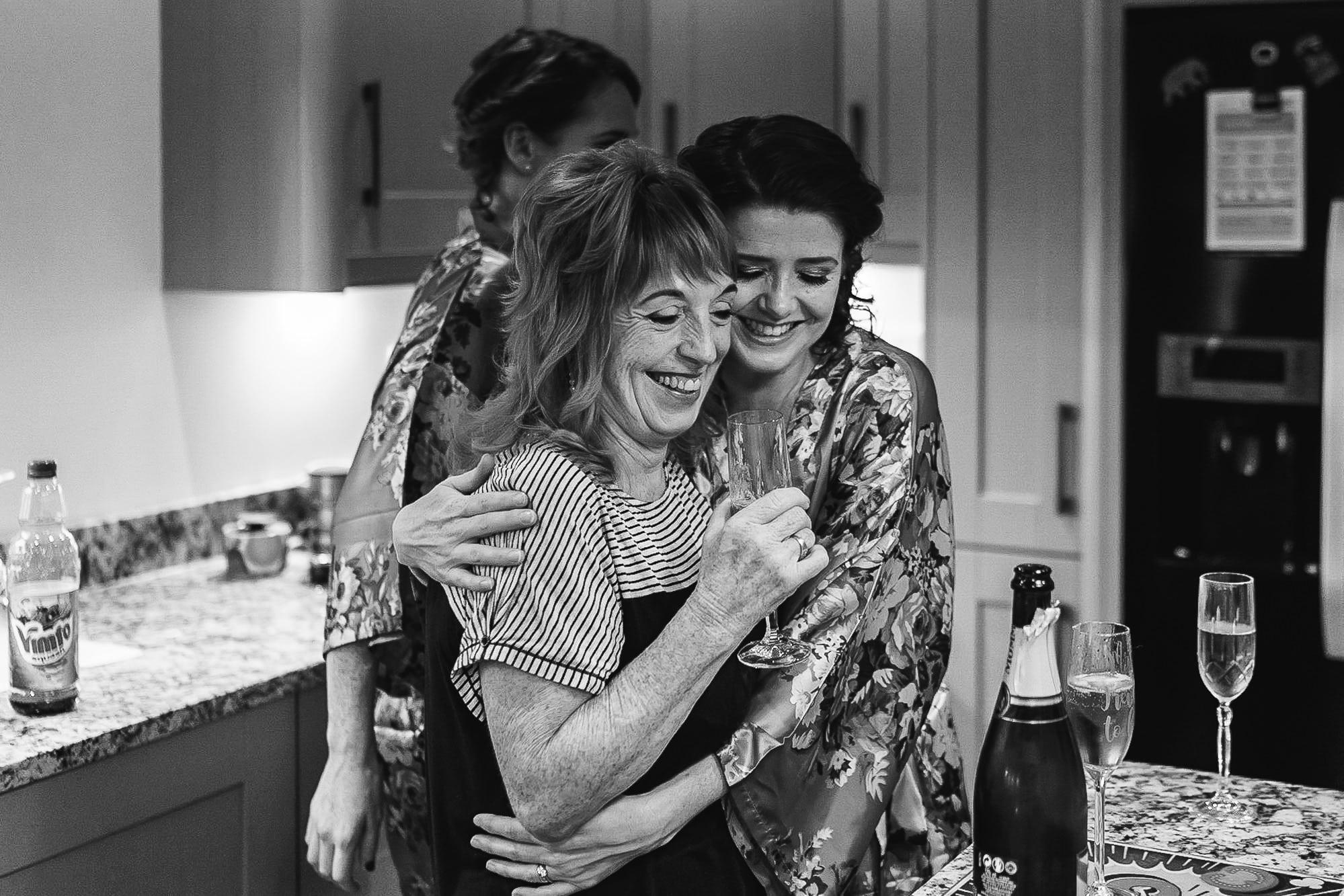 Bridesmaid hugging her mum