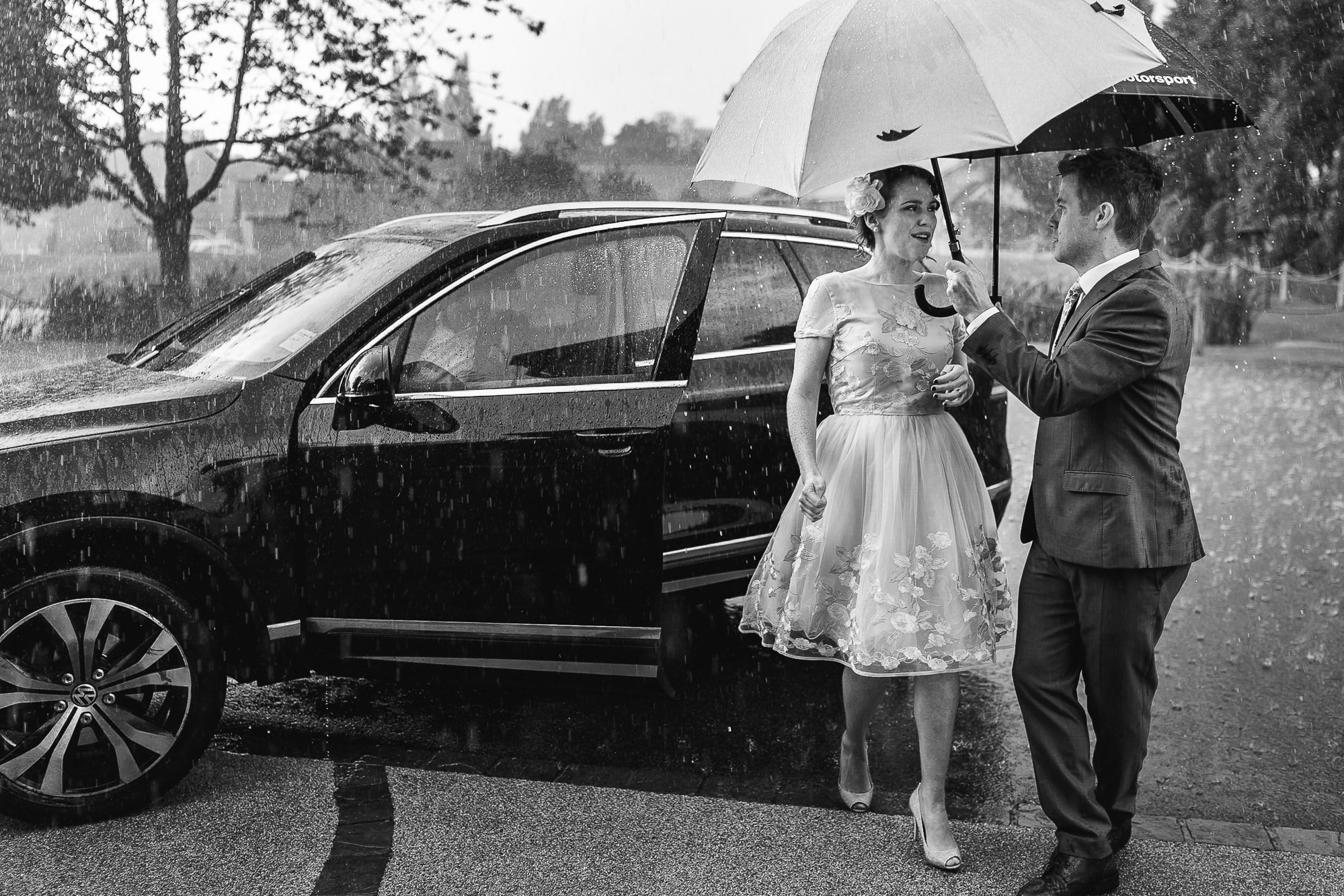 Bridesmaid walking into ceremony during rain at Colshaw Hall