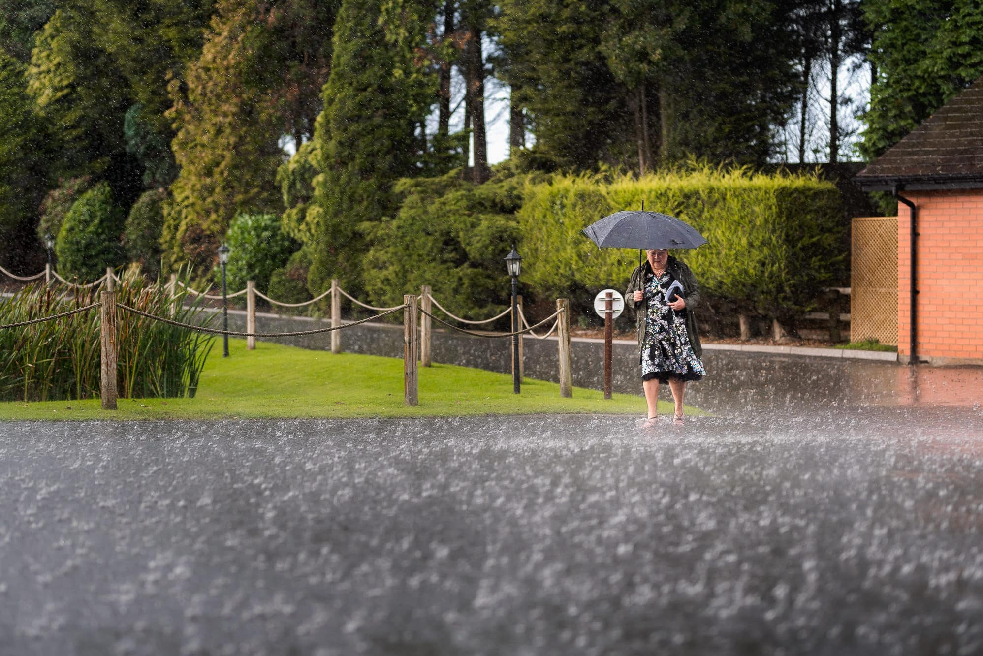 Mother of bride walking in rain at Colshaw Hall
